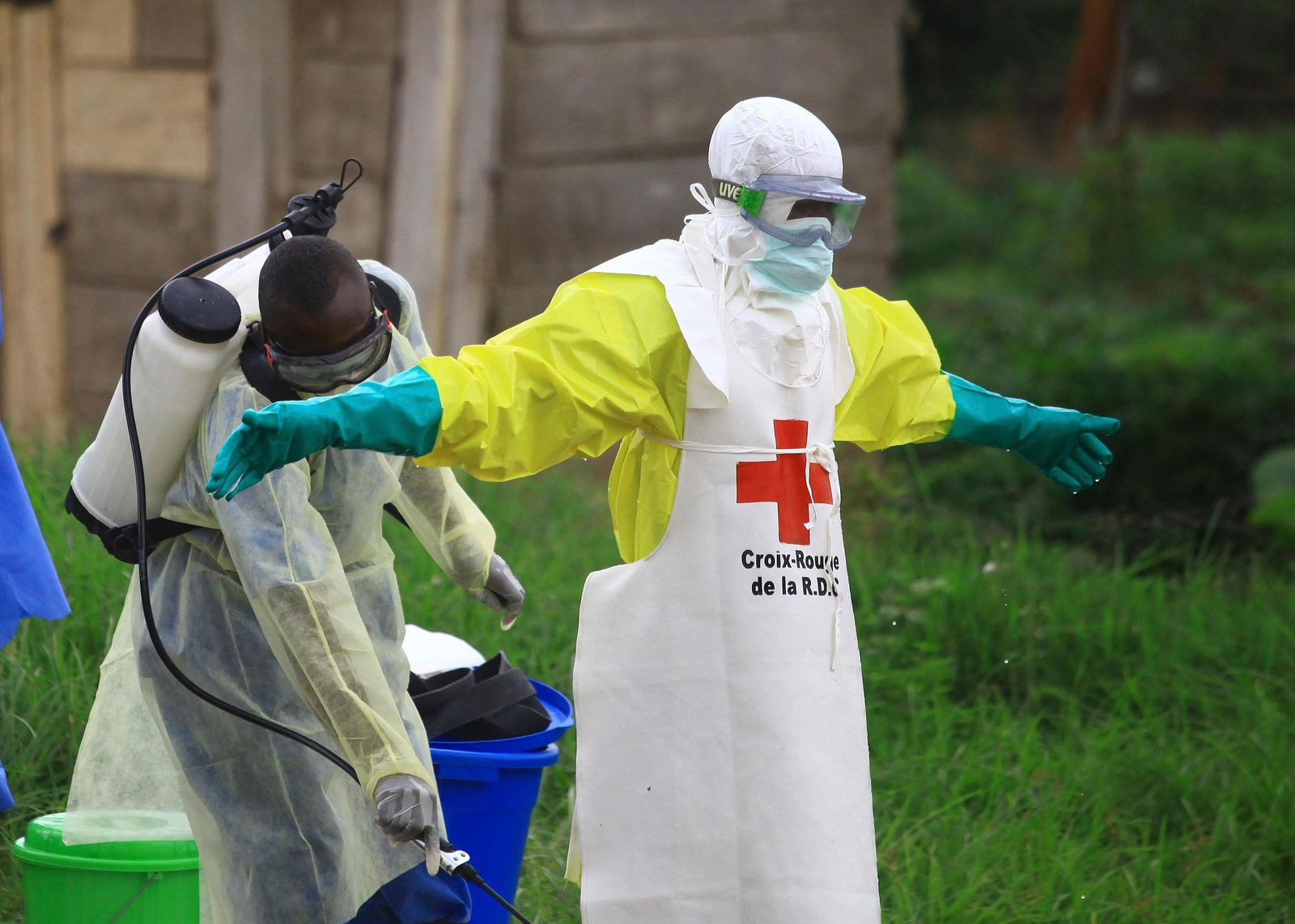 FILE - In this Sunday, Sept 9, 2018 file photo, a health worker sprays disinfectant on his colleague after working at an Ebola treatment centre in Beni, Eastern Congo. (AP Photo/Al-hadji Kudra Maliro, FILE)