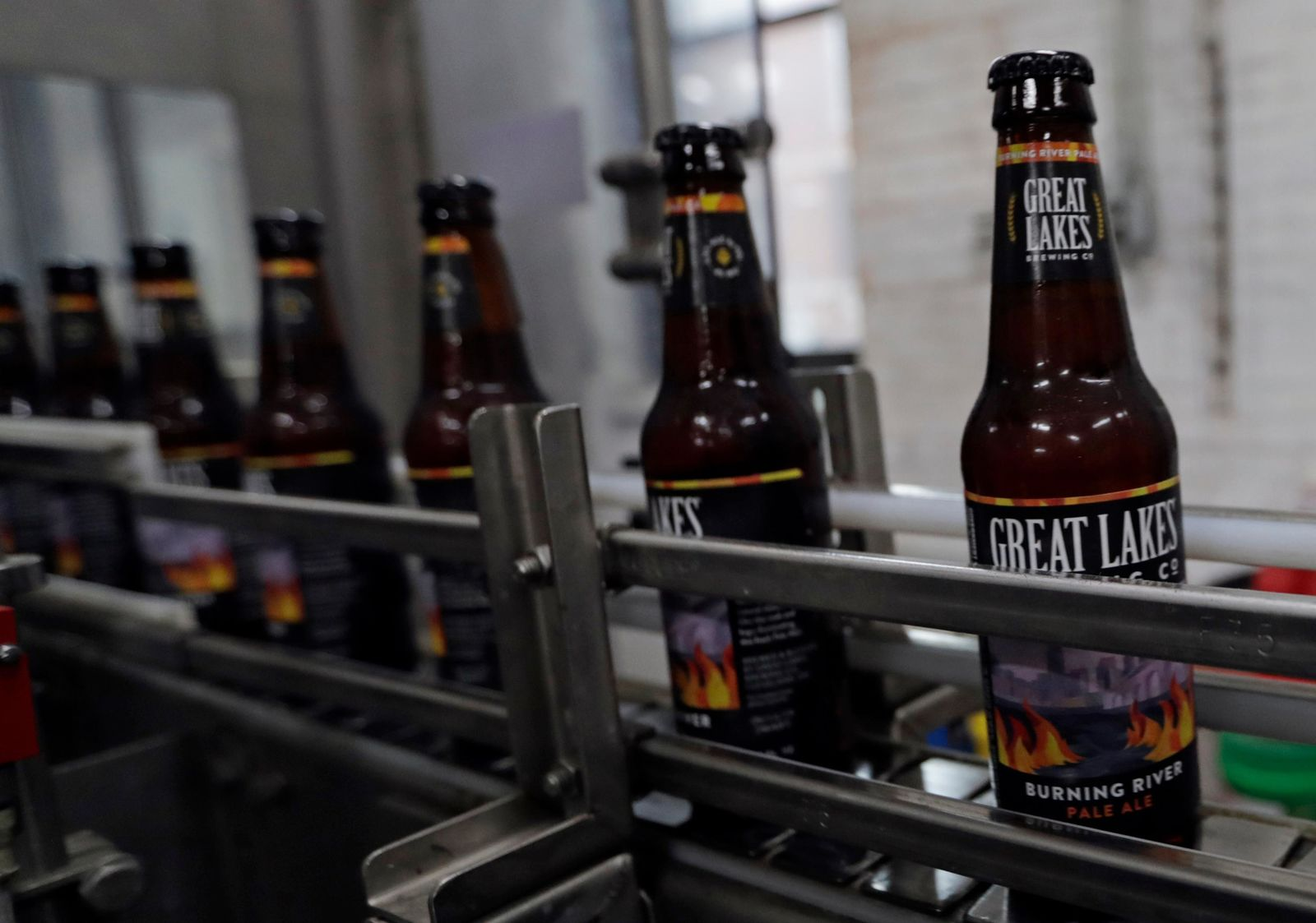 "Bottles of Burning River beer make their way down the assembly line in the bottling process at the Great Lakes Brewing Company, Monday, June 17, 2019, in Cleveland. The ""burning river"" in the beer's name is inspired by the Cuyahoga River's most famous fire. (AP Photo/Tony Dejak)"