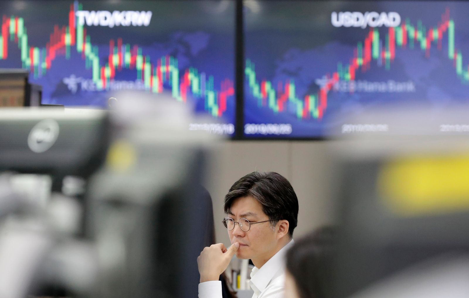 A currency trader watches the computer monitors near the screens showing the foreign exchange rates at the foreign exchange dealing room in Seoul, South Korea, Monday, Sept. 16, 2019. (AP Photo/Lee Jin-man)