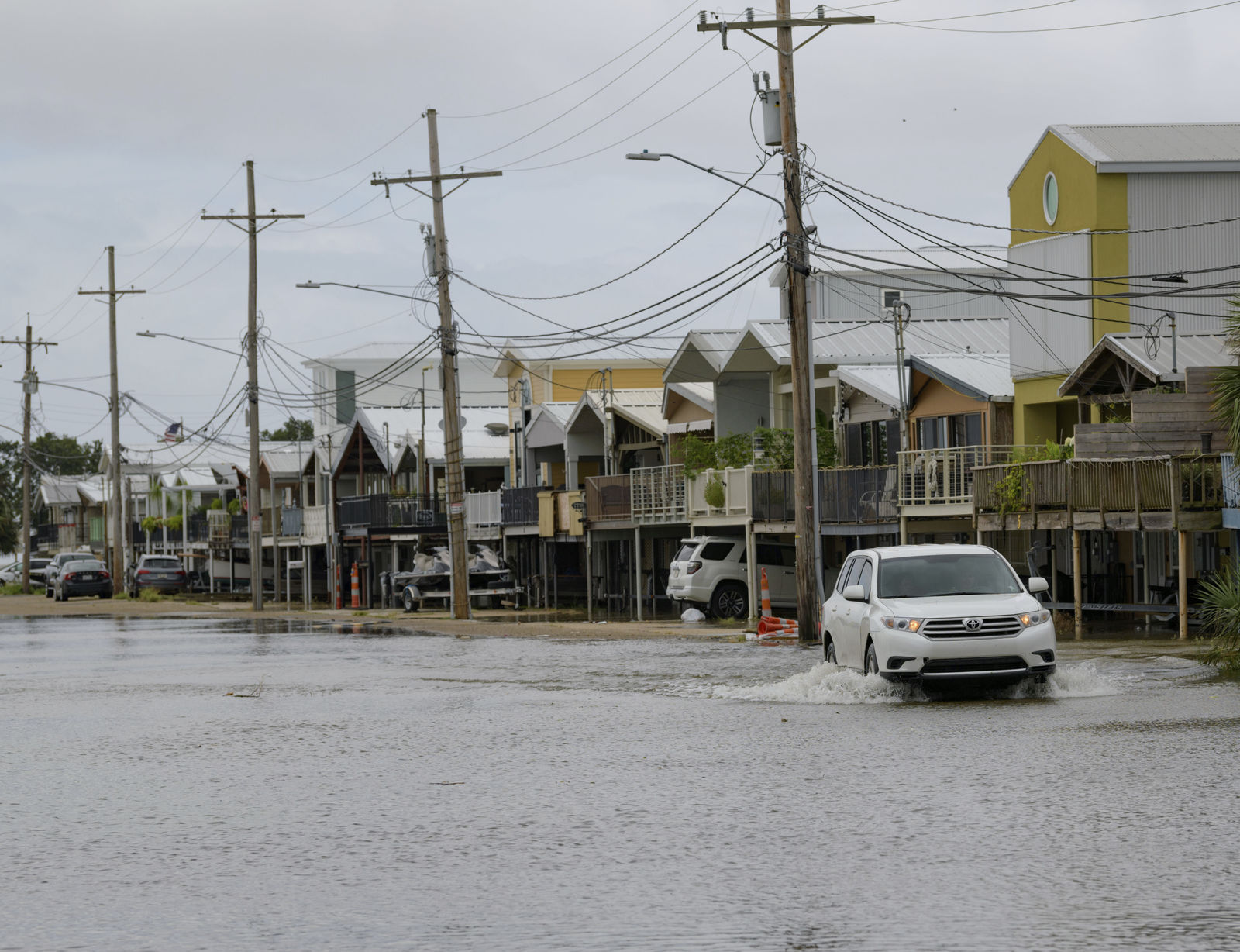 An SUV travels down Breakwater Drive in New Orleans, La., Friday, July 12, 2019, near the Orleans Marina as water moves in from Lake Pontchartrain from the storm surge from Tropical Storm Barry in the Gulf of Mexico. The area is behind a flood wall that protects the rest of the city. (AP Photo/Matthew Hinton)