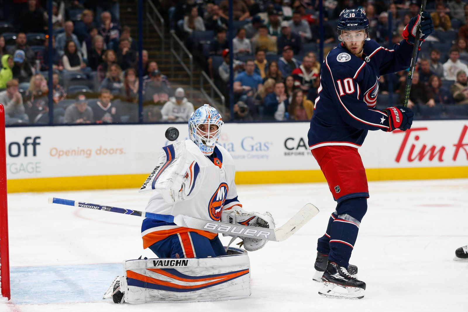 New York Islanders' Thomas Greiss, left, of Germany, makes a save in front of Columbus Blue Jackets' Alexander Wennberg, of Sweden, during the second period of an NHL hockey game Saturday, Oct. 19, 2019, in Columbus, Ohio. (AP Photo/Jay LaPrete)