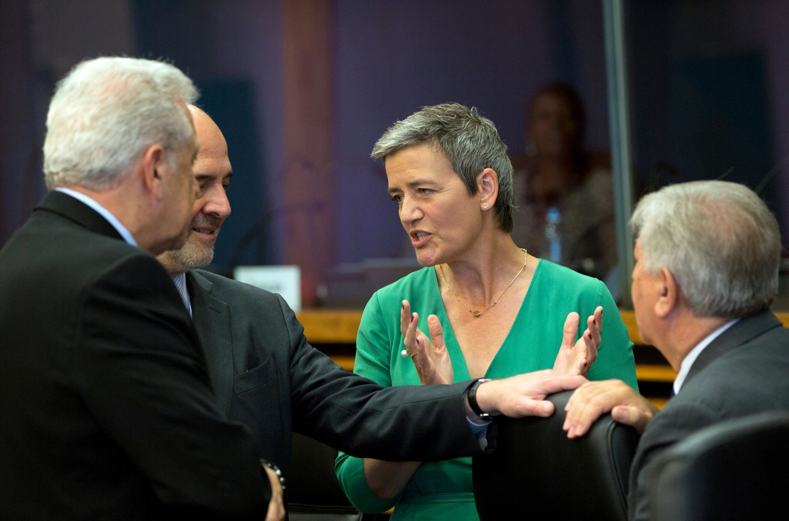 European Commissioner for Competition Margrethe Vestager, center, speaks with European Commissioner for Economic and Financial Affairs Pierre Moscovici, second left, and European Commissioner for Migration and Home Affairs Dimitris Avramopoulos, left, during the weekly college meeting at EU headquarters in Brussels, Wednesday, July 3, 2019. (AP Photo/Virginia Mayo)