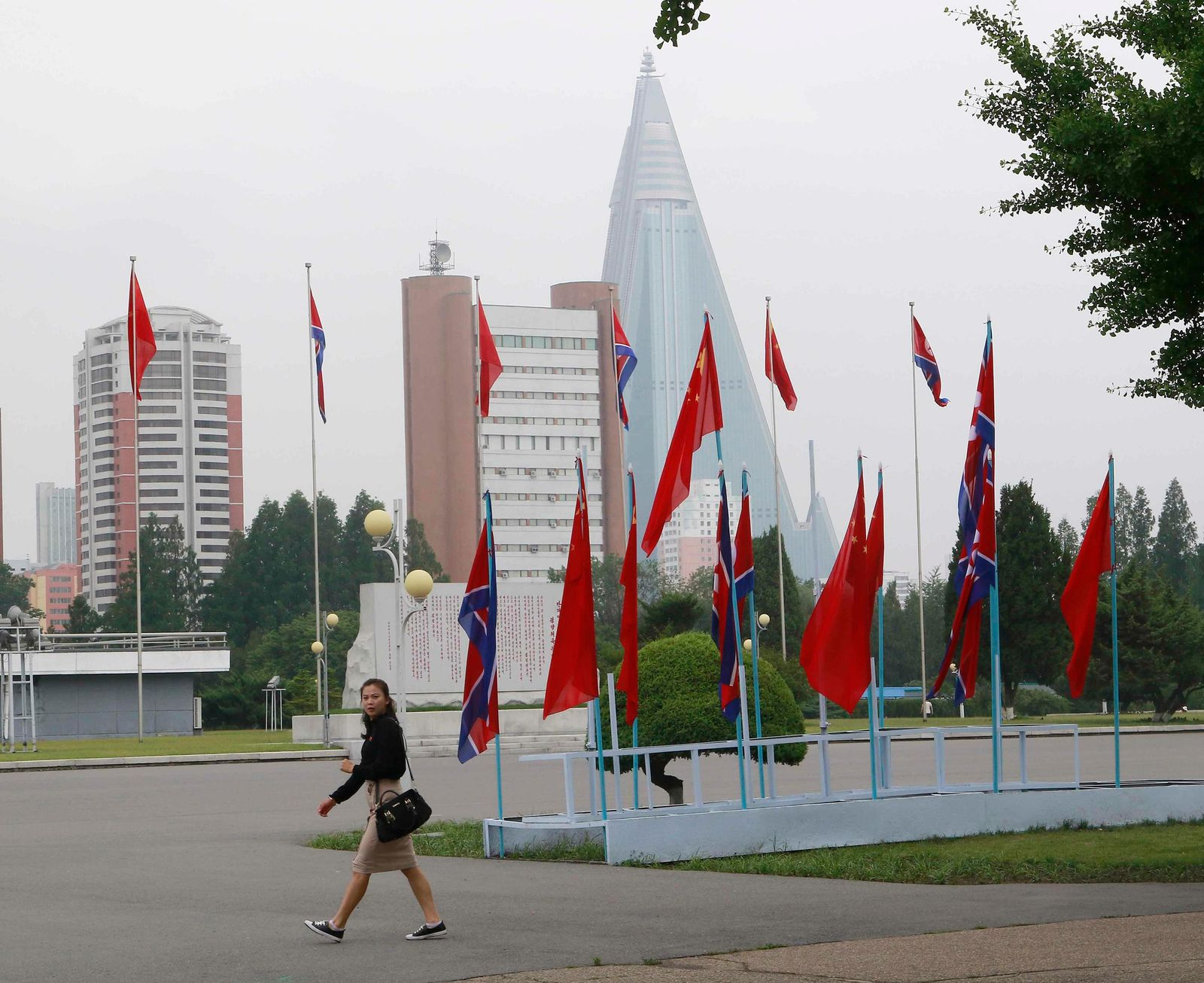 A woman walks past North Korean and Chinese national flags hoisted on a street in Pyongyang, North Korea Thursday, June 20, 2019. Chinese President Xi Jinping arrived Thursday morning for a two-day state visit to North Korea, where he is expected to talk with leader Kim Jong Un about the stalled negotiations with Washington over North Korea's nuclear weapons. (AP Photo/Jon Chol Jin)