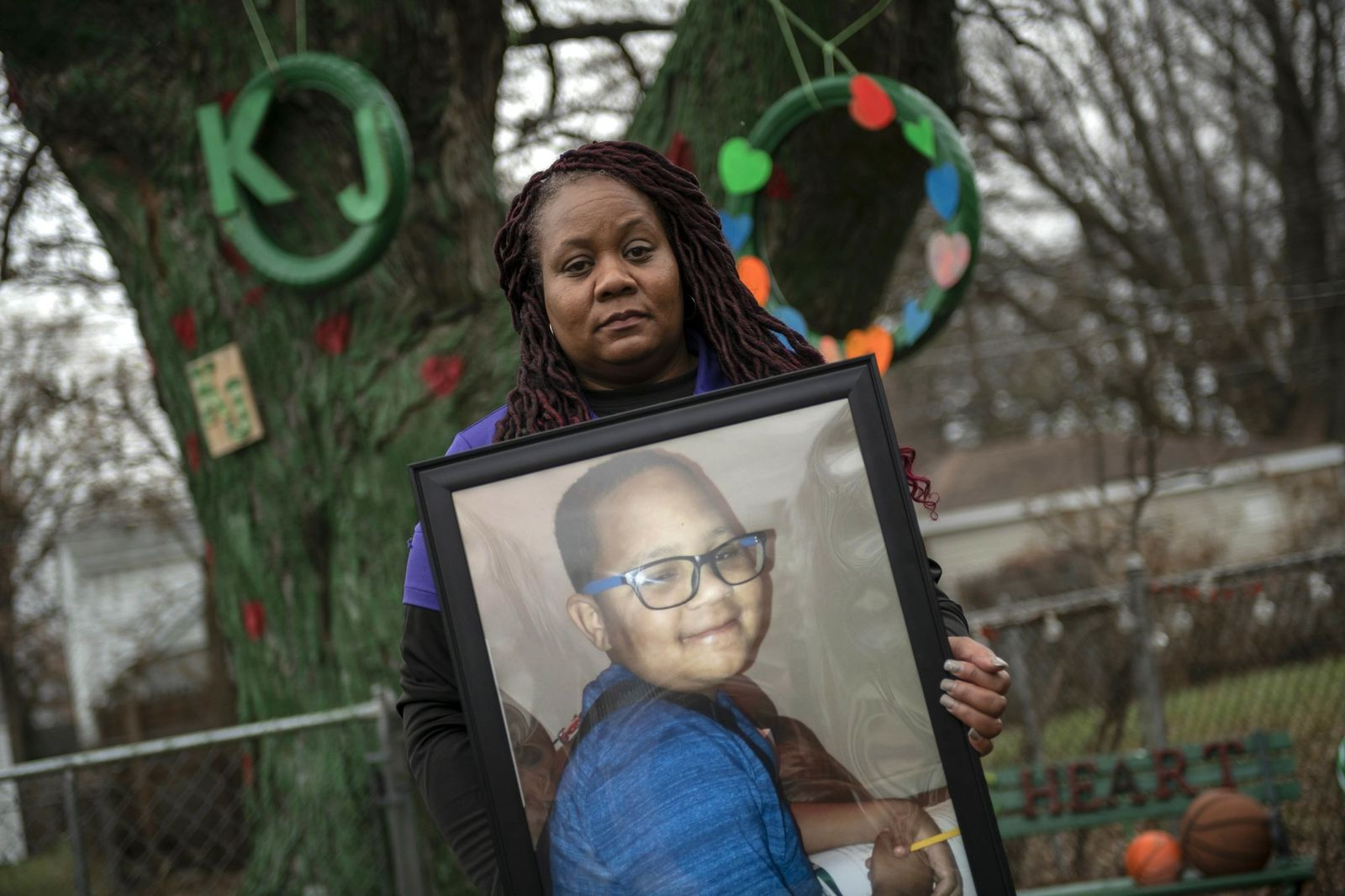 In this Dec. 3, 2018 photo, LaSondra Singleton holds a photo of her son Kenneth Gross Jr. while standing in front of a tree that was decorated in her son's honor at her Warren, Mich., home. (David Guralnick/Detroit News via AP)