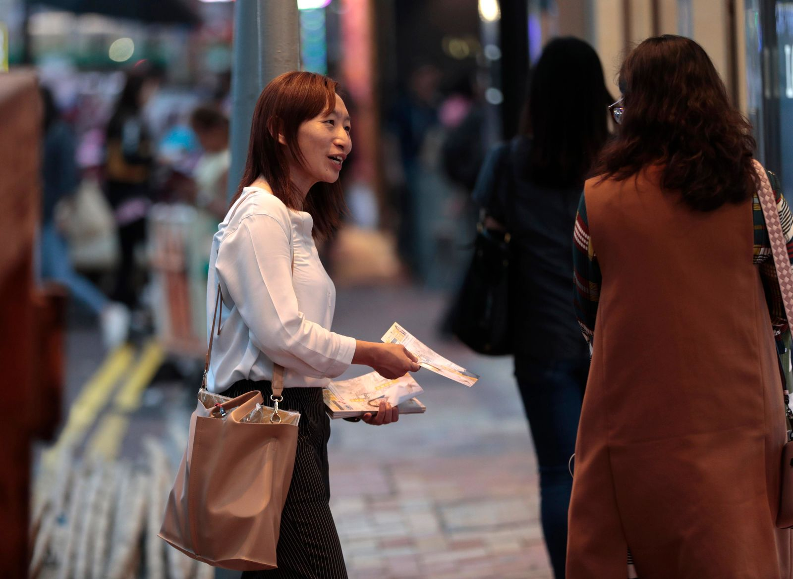 In this photo taken Thursday, Nov. 7, 2019, district council candidate Cathy Yau distributes flyers to pedestrians during her campaign at Causeway Bay in Hong Kong. Yau. a former police officer, grew exasperated as police used more force to quell the unrest. (AP Photo/Dita Alangkara)