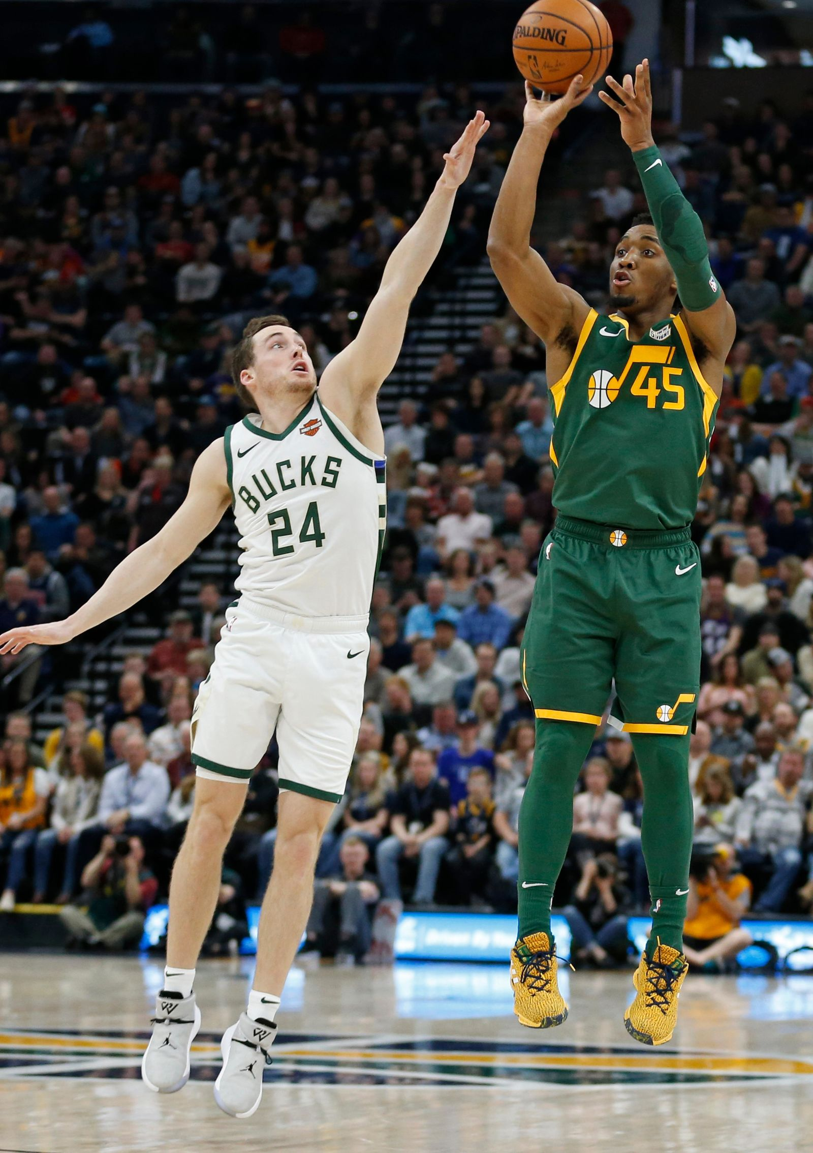 Utah Jazz guard Donovan Mitchell (45) shoots as Milwaukee Bucks guard Pat Connaughton (24) defends during the first half of an NBA basketball game Saturday, March 2, 2019, in Salt Lake City. (AP Photo/Rick Bowmer)