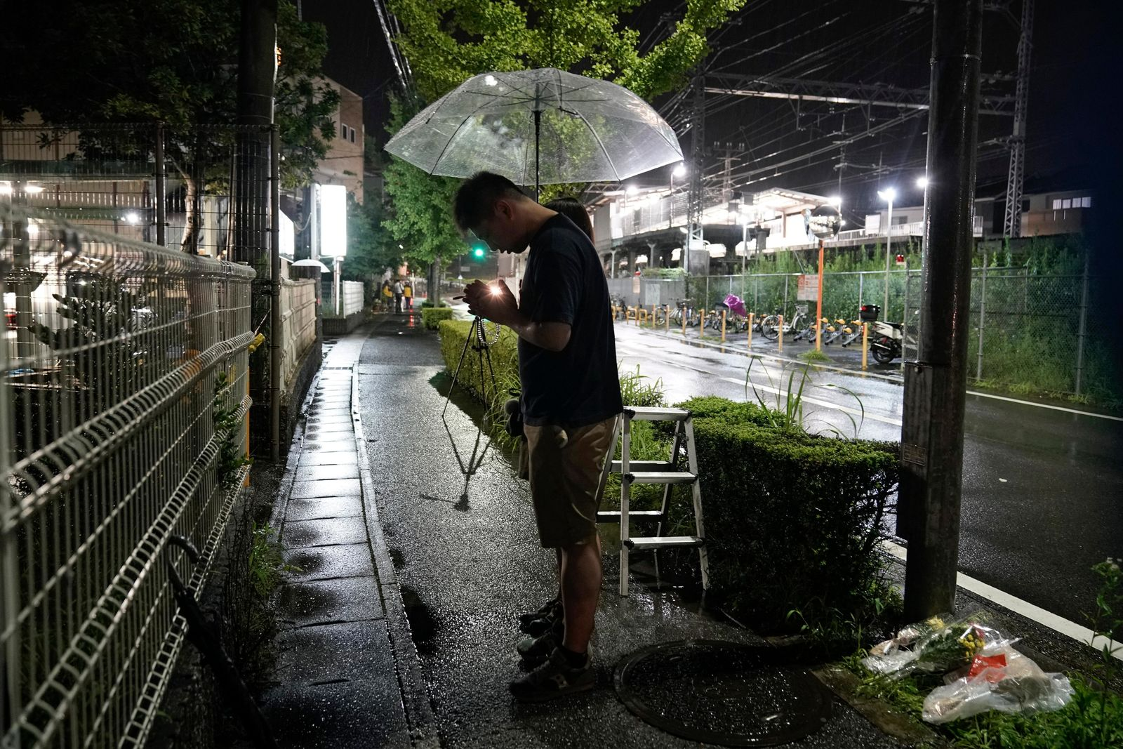 "A couple prays after placing flowers near the Kyoto Animation building, Friday, July 18, 2019, in Kyoto, Japan.   A man screaming ""You die!"" burst into an animation studio in Kyoto, doused it with a flammable liquid and set it on fire Thursday, killing several people in an attack that shocked the country and brought an outpouring of grief from anime fans. (AP Photo/Jae C. Hong)"