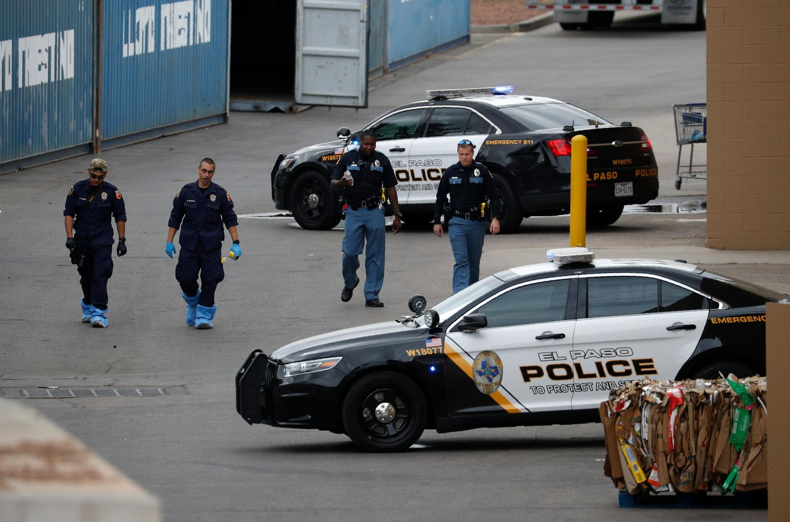 Police officers walk behind a Walmart at the scene of a mass shooting at a shopping complex Tuesday, Aug. 6, 2019, in El Paso, Texas. Patrick Crusius, 21, opened fire Saturday at the mall that largely caters to the local Mexican-American community. (AP Photo/John Locher)