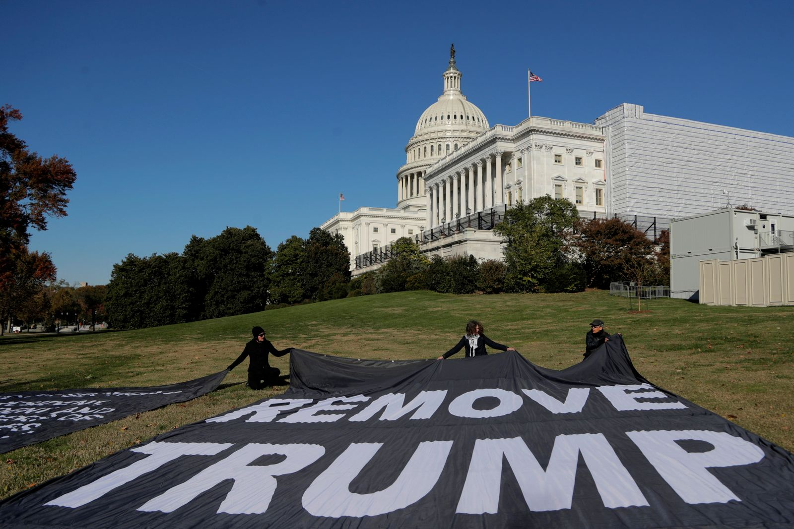 Demonstrators kneel near large banners on the lawn adjacent to the U.S. Capitol, while a top U.S. diplomat in Ukraine William Taylor, and career Foreign Service officer George Kent, testify before the House Intelligence Committee on Capitol Hill in Washington, Wednesday, Nov. 13, 2019, during the first public impeachment hearings of President Donald Trump's efforts to tie U.S. aid for Ukraine to investigations of his political opponents. (AP Photo/Julio Cortez)