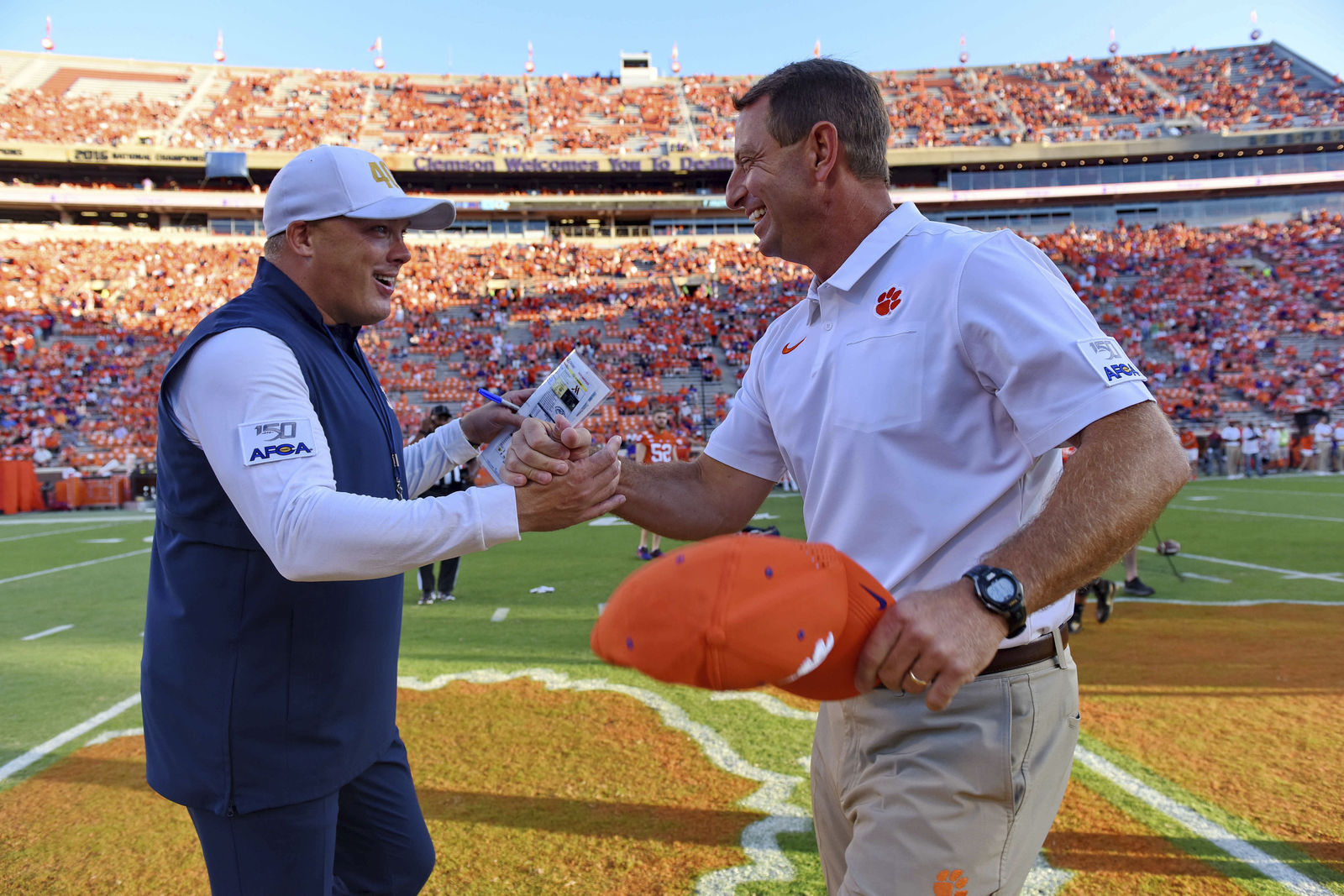 Clemson coach Dabo Swinney, right, greets Georgia Tech coach Geoff Collins before an NCAA college football game Thursday, Aug. 29, 2019, in Clemson, S.C. (AP Photo/Richard Shiro)