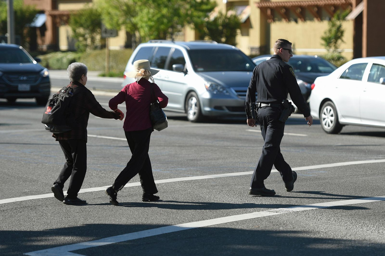 A police officer escorts pedestrians across El Camino Real near the scene of car crash at the intersection of El Camino Real and Sunnyvale Road in Sunnyvale, Calif., on Wednesday, April 24, 2019. Investigators are working to determine the cause of the crash in Northern California that injured several pedestrians on Tuesday evening. Authorities say the driver of the car was taken into custody after he appeared to deliberately plow into the group. (AP Photo/Cody Glenn)