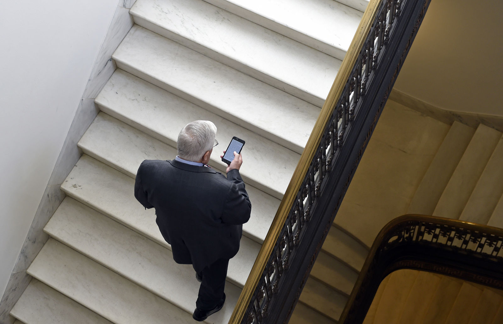 FILE - In this Feb. 4, 2015, file photo, Sen. Mike Enzi, R-Wyo., checks his phone as he arrives for a bipartisan lunch in the Kennedy Caucus Room on Capitol Hill in Washington. Oregon Sen. Ron Wyden is proposing new legislation that would allow the Senate's Sergeant at Arms to spend taxpayer money protecting senators' private email accounts and personal devices amid persistent anxieties over the digital security of the American midterm vote. (AP Photo/Susan Walsh, File)