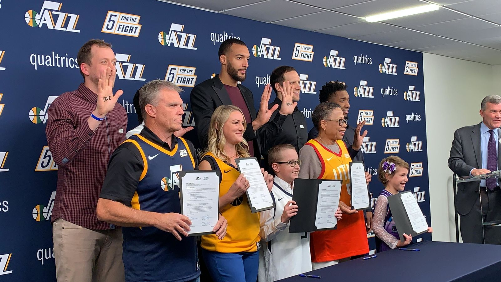 "Everyone poses for a photo op promoting ""5 For The Fight"" which aims to fund cancer research. (L-R) Joe Ingles (Jazz forward), Dave Warren (cancer fighter), Mike Conley (Jazz point guard), Dani Phillips (cancer fighter), Rudy Gobert (2-time Defensive Player of the Year, Utah Jazz Center) with Wyatt Page (young cancer fighter), Emma Houston (cancer fighter), Bojan Bogdanovic (Utah Jazz forward), Donovan ""Spida"" Mitchell (Utah Jazz guard) with Baylee Semrow (young cancer fighter), Jim Olson (Utah Jazz president). (Photo: Adam Forgie, KUTV)"