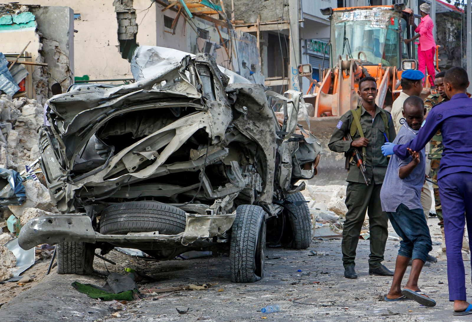 Security forces stand near the wreckage of an official vehicle that was destroyed in a bomb attack in the capital Mogadishu, Somalia Saturday, June 15, 2019. (AP Photo/Farah Abdi Warsameh)