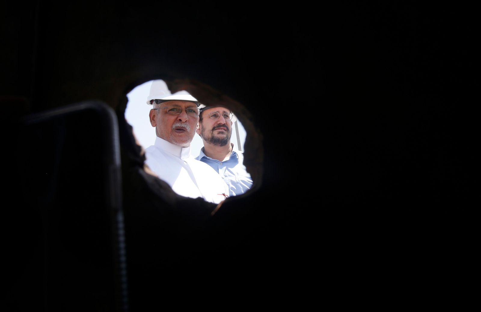 In this photo opportunity during a trip organized by Saudi information ministry, Aramco workers are seen through a hole in a damaged pipe in the Khurais oil field in Khurais, Saudi Arabia, Friday, Sept. 20, 2019, after it was hit during Sept. 14 attack. Saudi officials brought journalists Friday to see the damage done in an attack the U.S. alleges Iran carried out. (AP Photo/Amr Nabil)