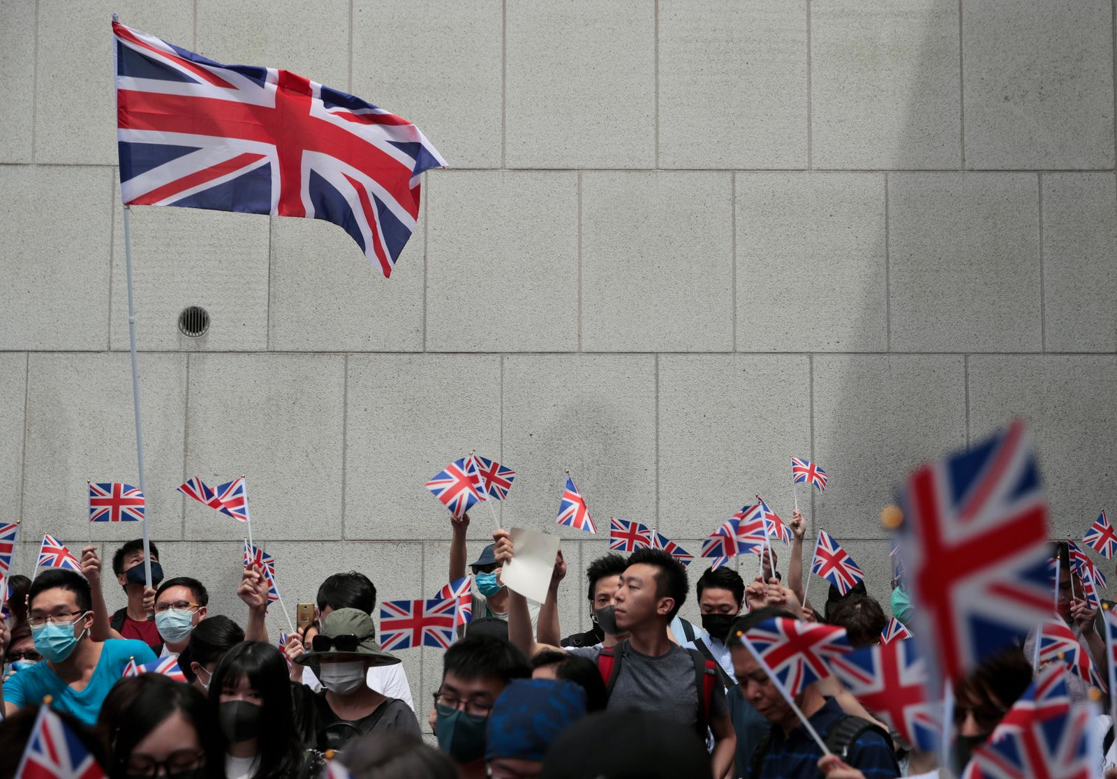 Protestors wave British flags and participate in a peaceful demonstration outside the British Consulate in Hong Kong, Sunday, Sept. 1, 2019.{ } (AP Photo/Jae C. Hong)