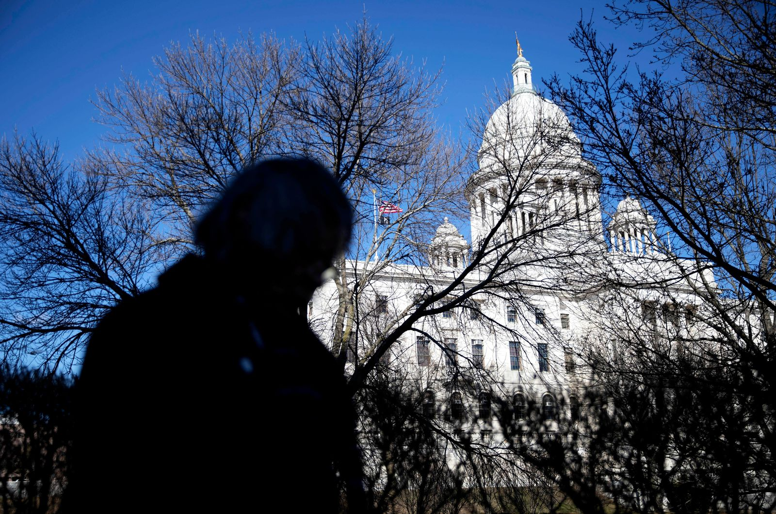FILE - In this Sunday, March 1, 2020 file photo, a pedestrian walks past the State House in Providence, R.I., as the state confirmed its first case of COVID-19.{ } (AP Photo/David Goldman)