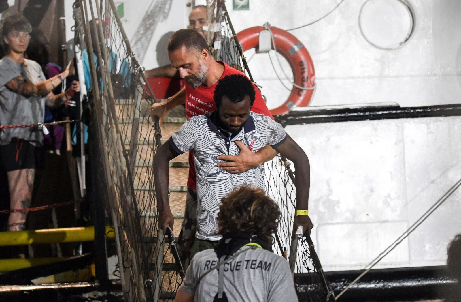 In this photo taken on Tuesday, Aug. 20, 2019, a man is helped disembark from the Open Arms rescue ship on the Sicilian island of Lampedusa, southern Italy. (AP Photo/Salvatore Cavalli)