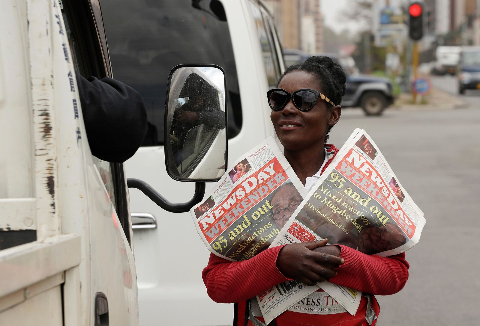 A vendor sells newspapers on a street in Harare, Zimbabwe, Saturday, Sept. 7, 2019. (AP Photo/Themba Hadebe)