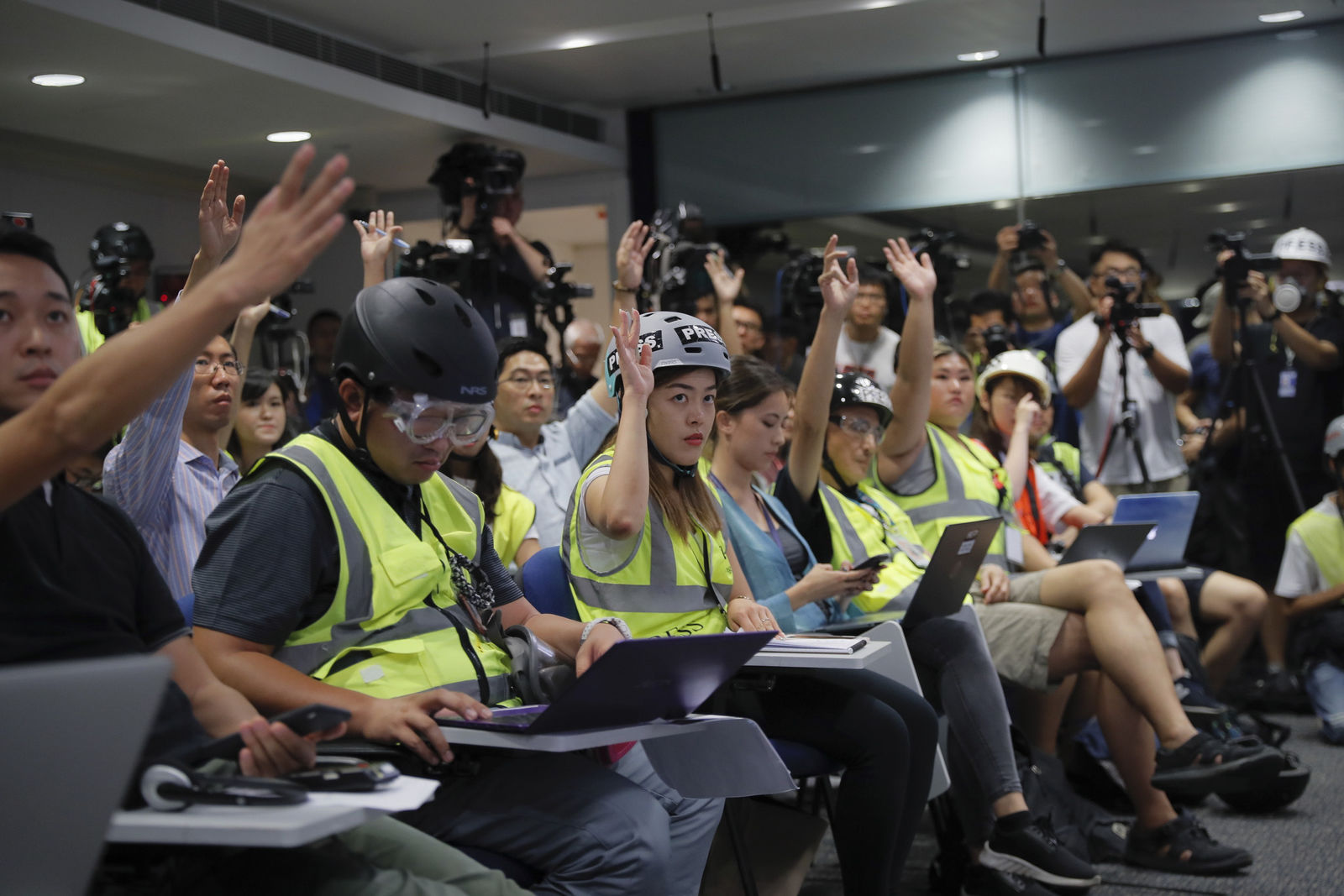 In a sign of protest against the police using force against the media, journalists wear protective gear during a police media conference in Hong Kong, Monday, Sept. 9, 2019.. (AP Photo/Kin Cheung)