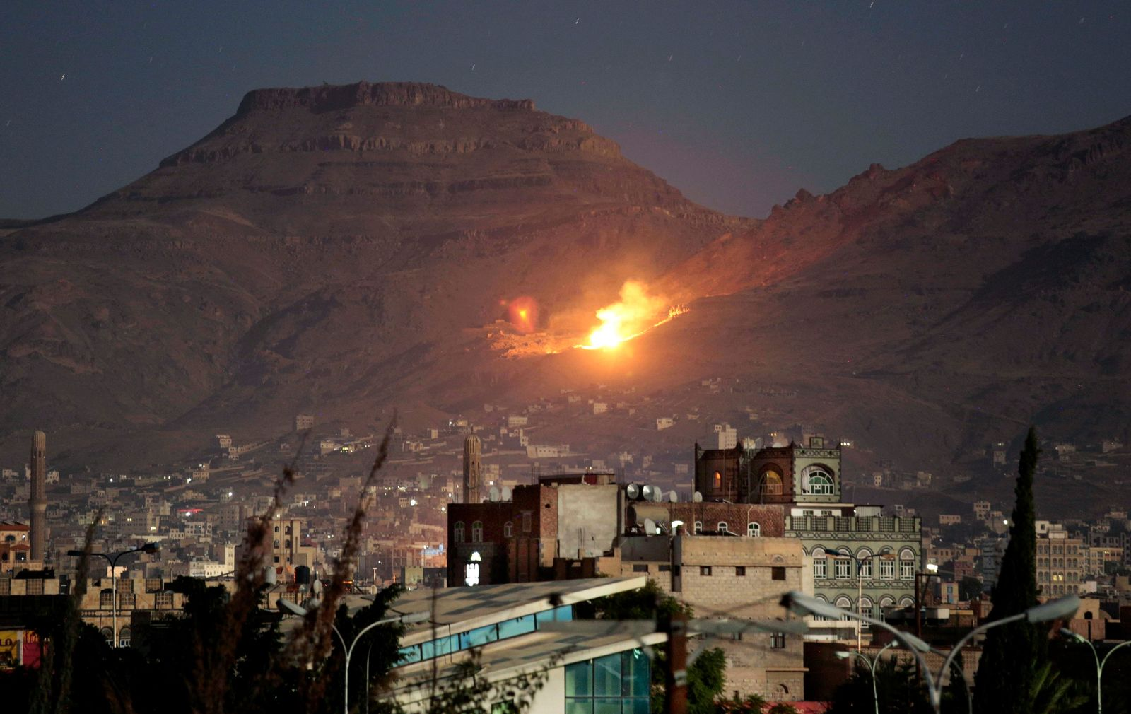 FILE - In this Oct. 14, 2016 file photo, fire and smoke rise after a Saudi-led airstrike hit a site believed to be one of the largest weapons depots on the outskirts of Yemen's capital, Sanaa. . (AP Photo/Hani Mohammed, File)