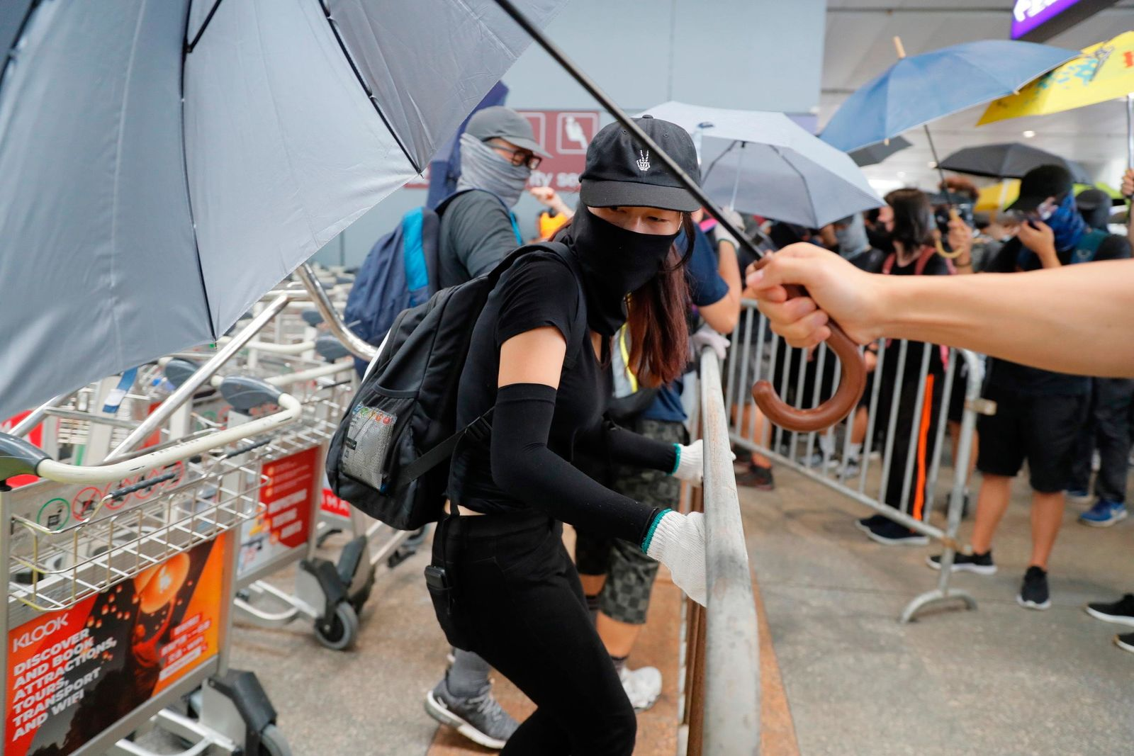 A protestor uses an umbrella to hide the identity of another as pro-democracy protestors create blockades outside the airport in, Hong Kong, Sunday, Sept.1, 2019.(AP Photo/Kin Cheung)