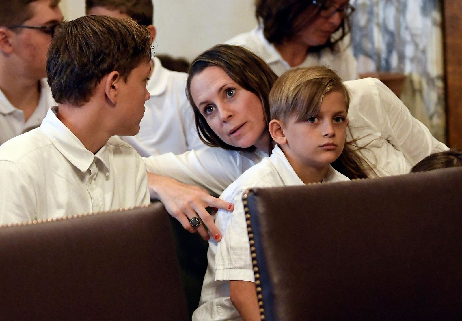 FILE - In this Aug. 14, 2019, file photo, Leslie Danesi, center, sits with her children Lorenzo Danesi, left, and Gabriel Danes, right, as attorneys prepare to speak at a hearing challenging the constitutionality of the state legislature's repeal of the religious exemption to vaccination in Albany, N.Y.(AP Photo/Hans Pennink, File)