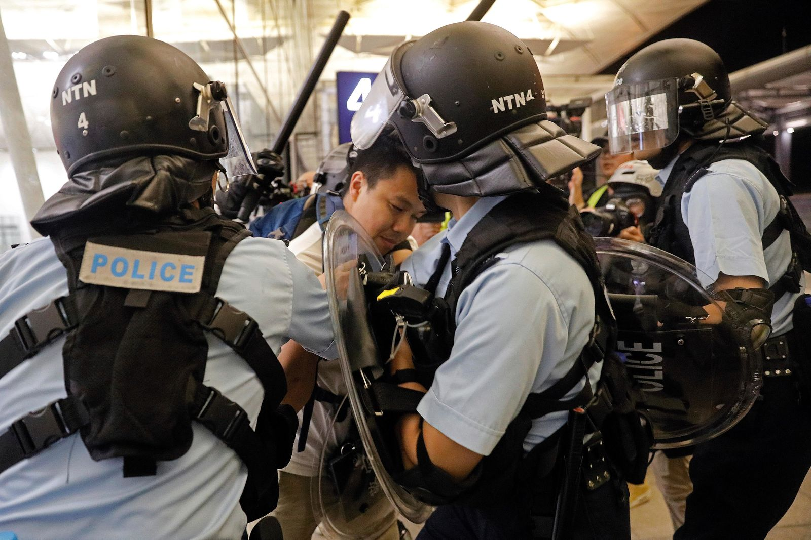 Policemen arrest a protester during a demonstration at the Airport in Hong Kong, Tuesday, Aug. 13, 2019. (AP Photo/Vincent Yu)