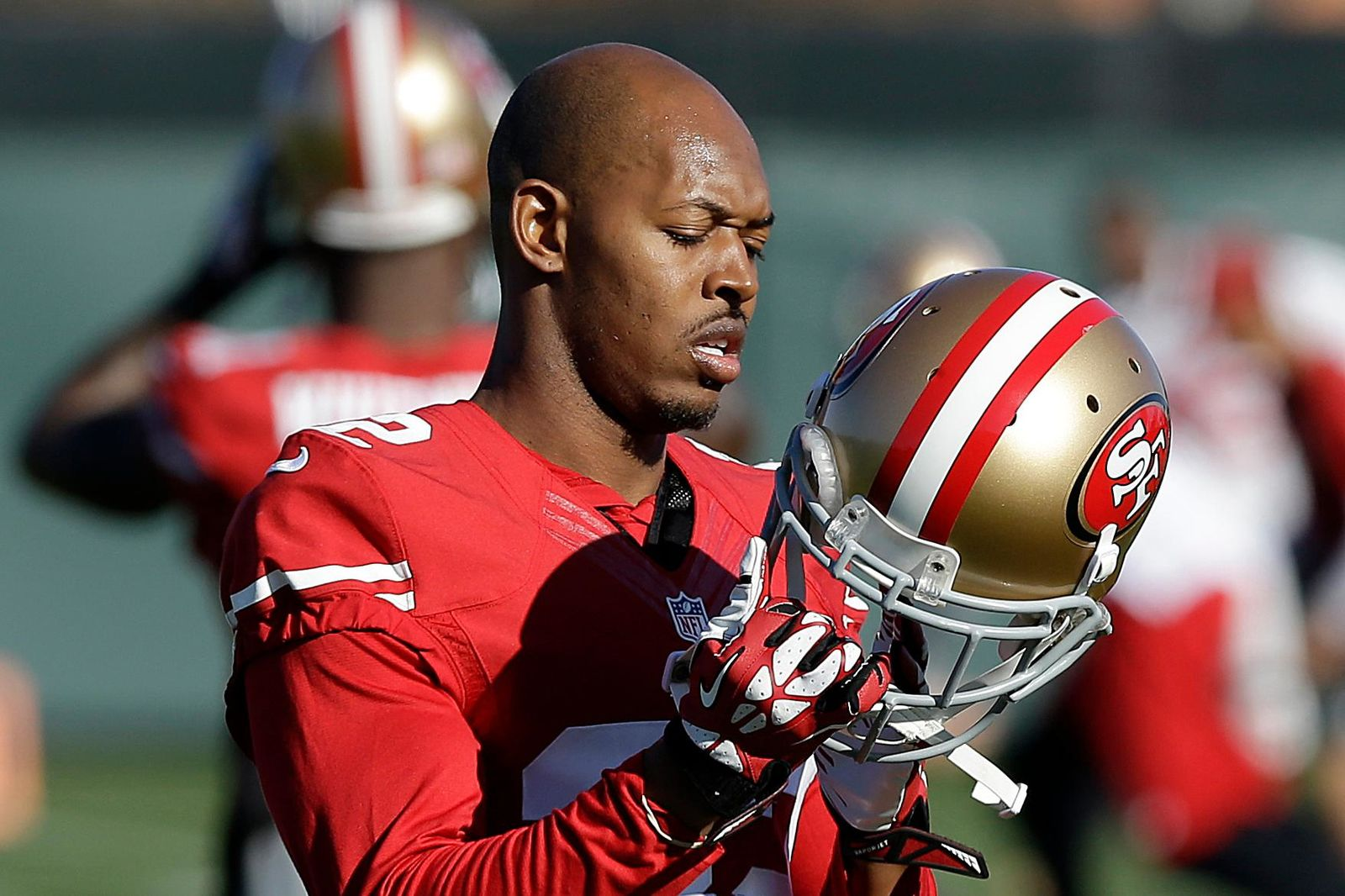 FILE - In this Jan. 15, 2014 file photo, San Francisco 49ers cornerback Carlos Rogers adjusts his helmet during practice at an NFL football training facility in Santa Clara, Calif. Ten former NFL players have been charged with defrauding the league's healthcare benefit program. They include five who played on the Washington Redskins, including Clinton Portis and Carlos Rogers.  (AP Photo/Jeff Chiu)