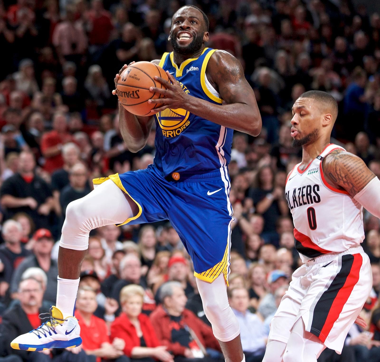 Golden State Warriors forward Draymond Green, left, prepares to shoot over Portland Trail Blazers guard Damian Lillard during the first half of Game 3 of the NBA basketball playoffs Western Conference finals Saturday, May 18, 2019, in Portland, Ore. (AP Photo/Craig Mitchelldyer)