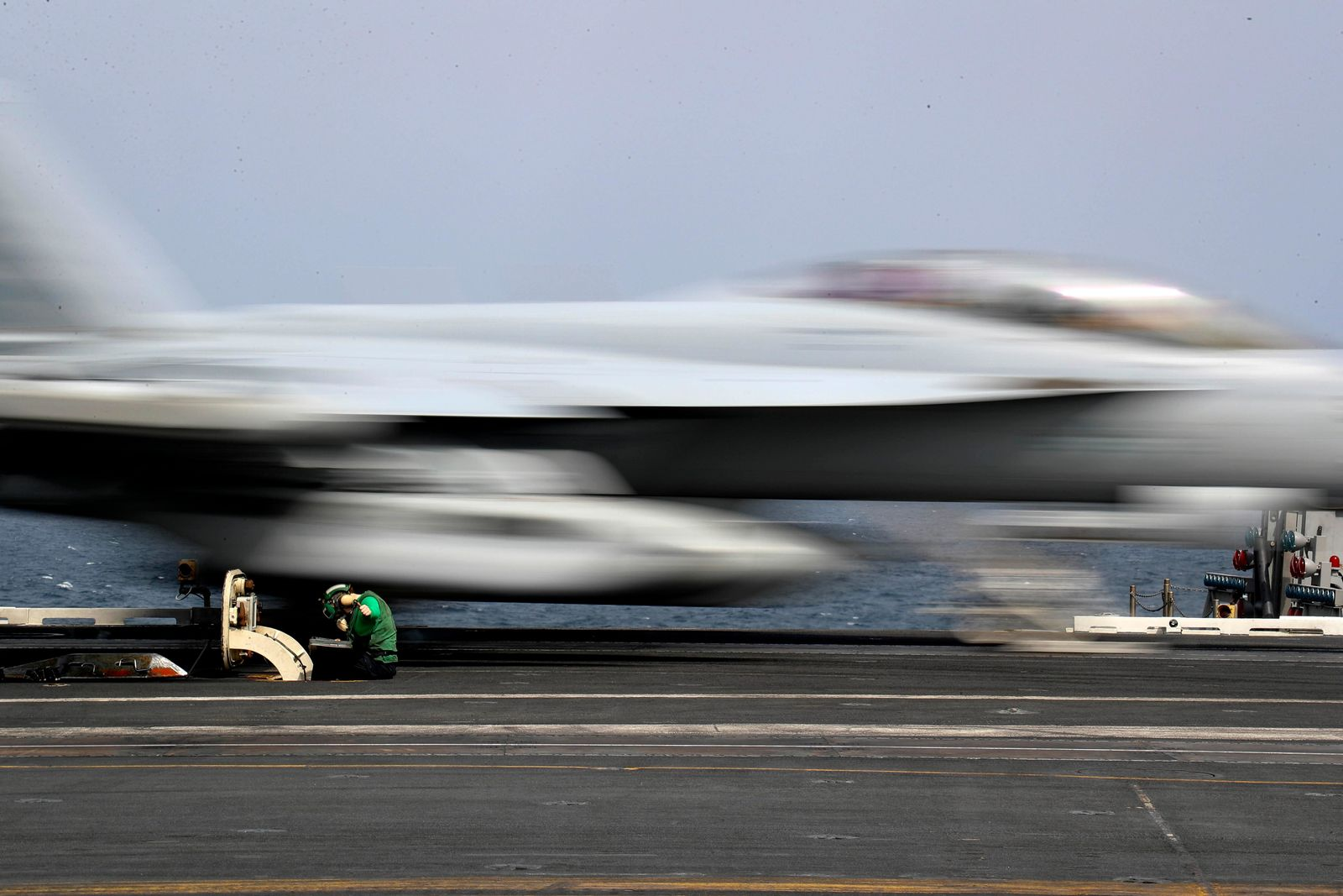 In this Thursday, May 16, 2019 photograph released by the U.S. Navy, Aviation Boatswain's Mate Airman Kayla Pettit operates a center deck station as an F-18 Super Hornet takes off from the USS Abraham Lincoln aircraft carrier in the Arabian Sea. (Mass Communication Specialist 3rd Class Jeff Sherman, U.S. Navy via AP)