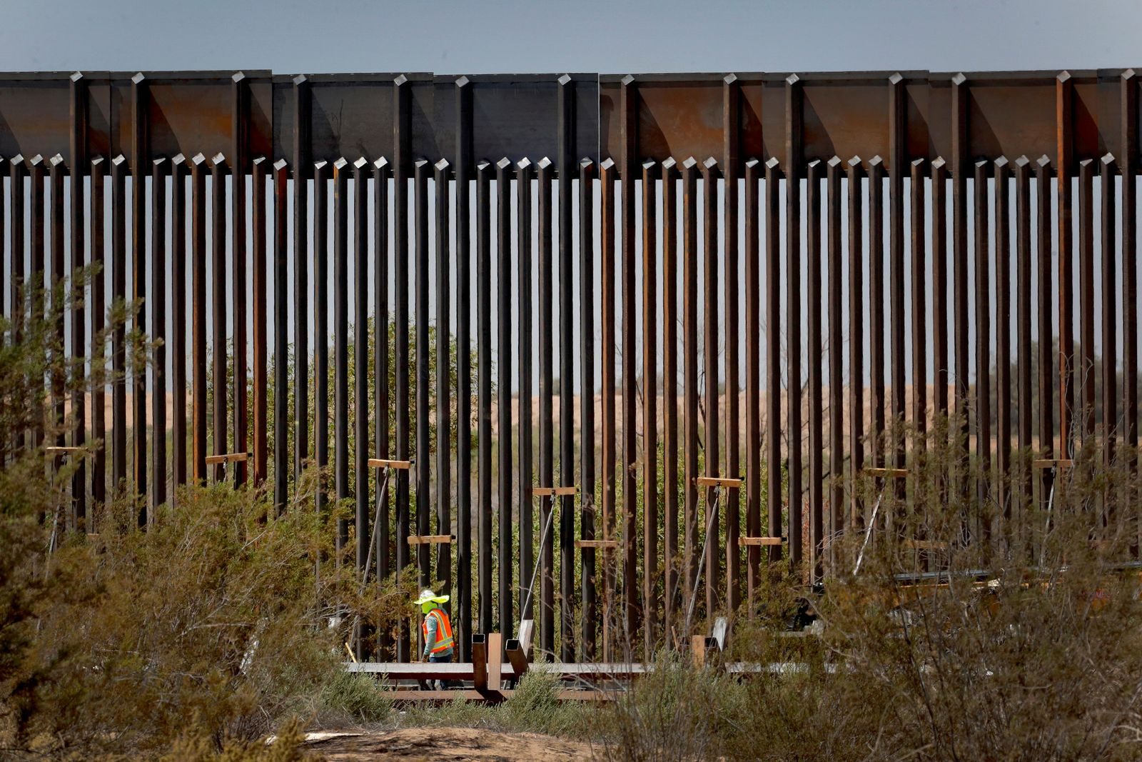 A government contractor walks beside a completed section of Pentagon-funded border wall along the Colorado River, Tuesday, Sept. 10, 2019 in Yuma, Ariz. The 30-foot high wall replaces a five-mile section of Normandy barrier and post-n-beam fencing along the the International border that separates Mexico and the United States. Construction began as federal officials revealed a list of Defense Department projects to be cut to pay for President Donald Trump's wall. (AP Photo/Matt York)
