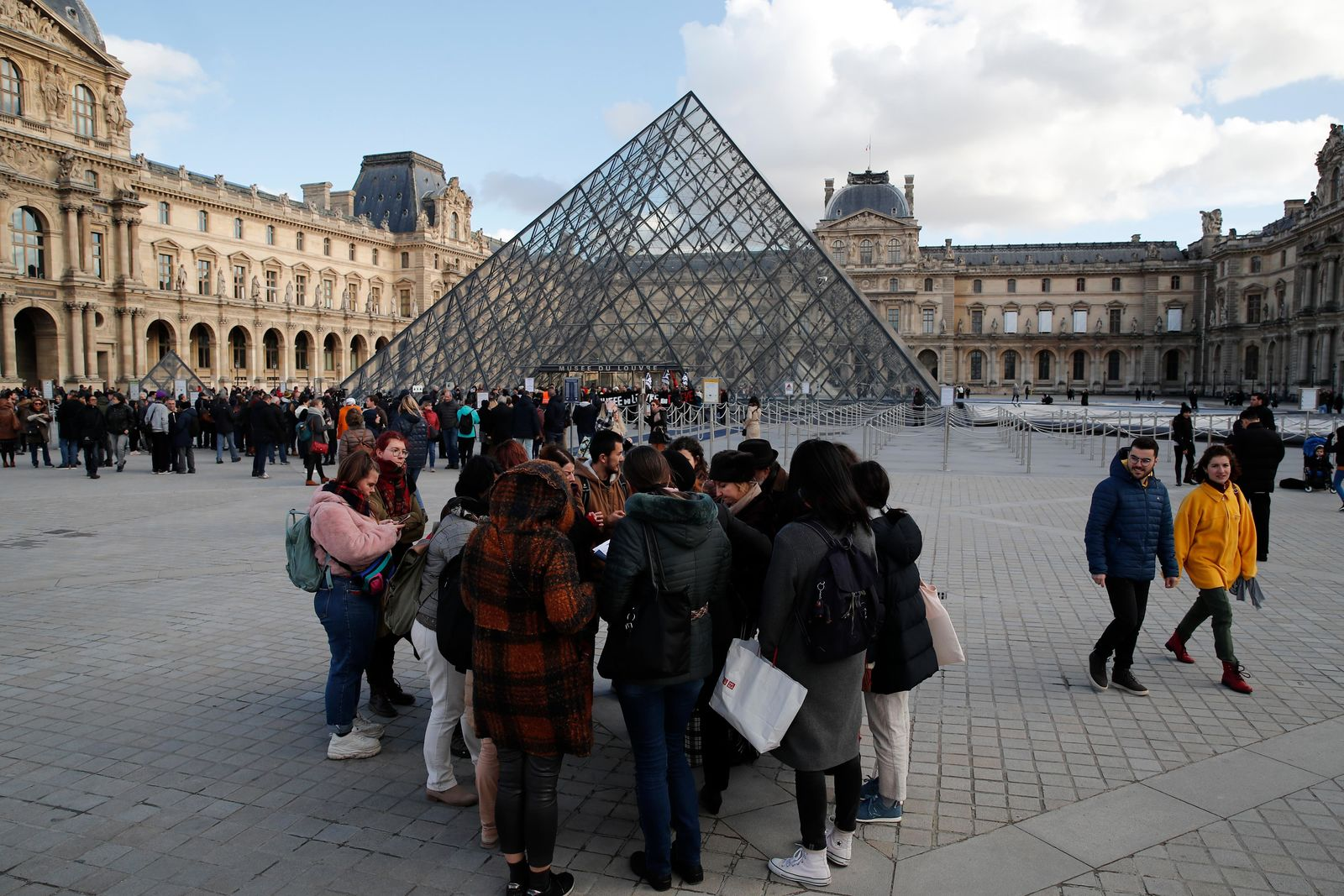 Visitors wait as striking employees demonstrate outside the Louvre museum Friday, Jan. 17, 2020 in Paris. . (AP Photo/Francois Mori)