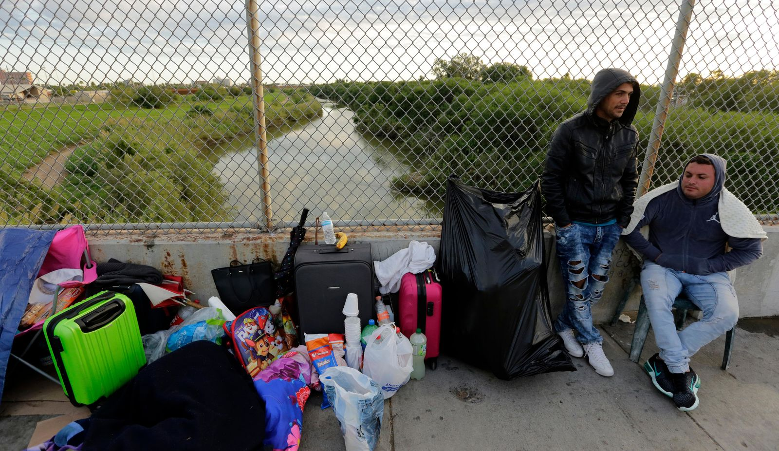 FILE - In this Nov. 2, 2018, file photo, Yenly Morales,left, and Yenly Herrera, right, immigrants from Cuba seeking asylum in the United States, wait on the Brownsville and Matamoros International Bridge in Matamoros, Mexico.{ } (AP Photo/Eric Gay, File)