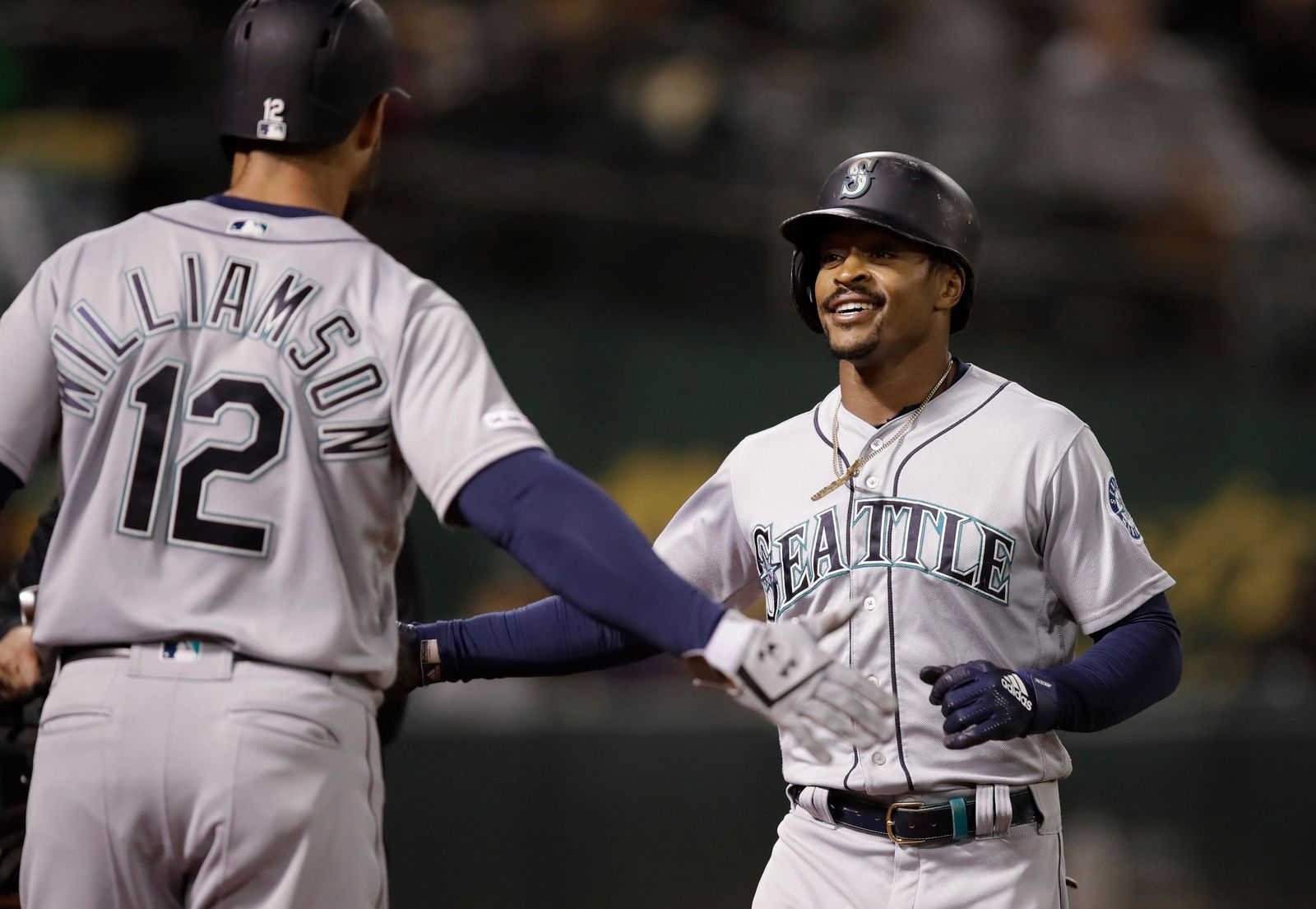 Seattle Mariners' Mallex Smith, right, celebrates with Mac Williamson after hitting a two-run home run off Oakland Athletics' Aaron Brooks during the eighth inning of a baseball game Friday, June 14, 2019, in Oakland, Calif. (AP Photo/Ben Margot)