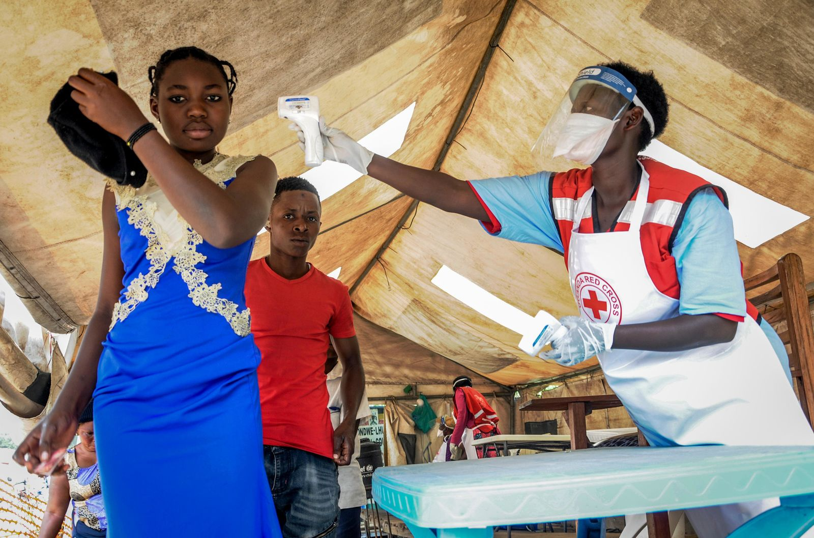 People coming from Congo have their temperature measured to screen for symptoms of Ebola, at the Mpondwe border crossing with Congo, in western Uganda Friday, June 14, 2019{ } (AP Photo/Ronald Kabuubi)