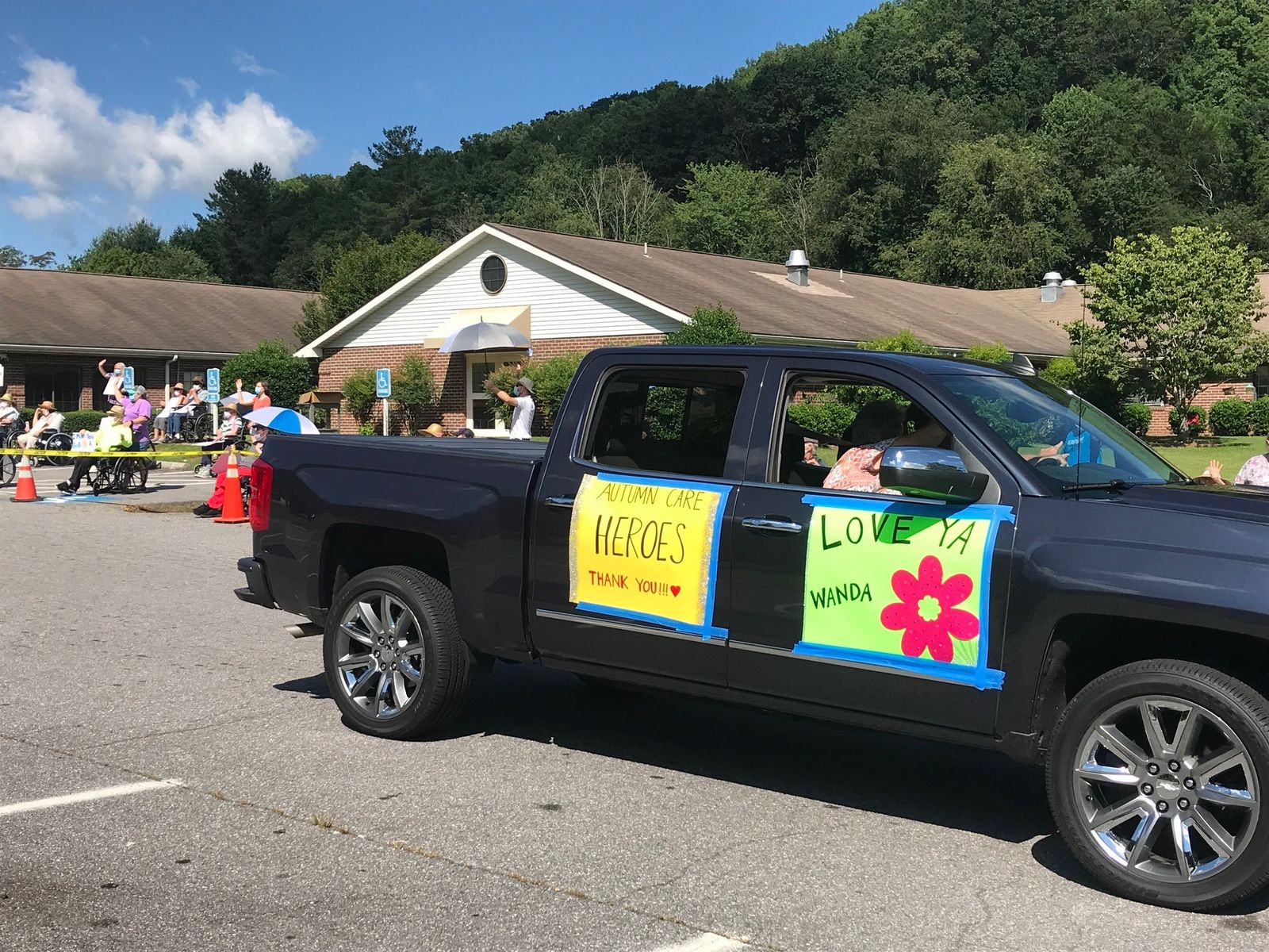 Local law enforcement, fire and EMS staff led the way in greeting about 70 residents gathered outside of Autumn Care of Waynesville on July 11 who haven't been able to visit with loved ones for about four months due to the pandemic. (Photo credit: WLOS Staff)