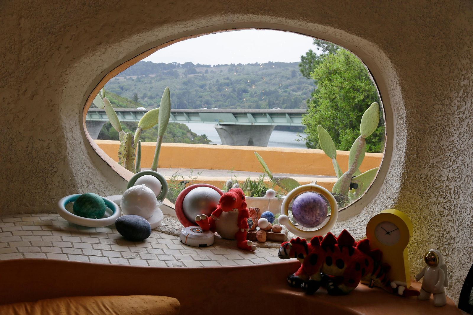 "In this photo taken Monday, April 1, 2019, a window in a sunken room called ""The Happy Place,"" looks out on Interstate 280 from inside the Flintstone House in Hillsborough, Calif.  The latest battle in the war between government rules and property rights is playing out in the posh San Francisco suburb, where a retired publishing mogul has installed an elaborate homage to ""The Flintstones"" family.    (AP Photo/Eric Risberg)"