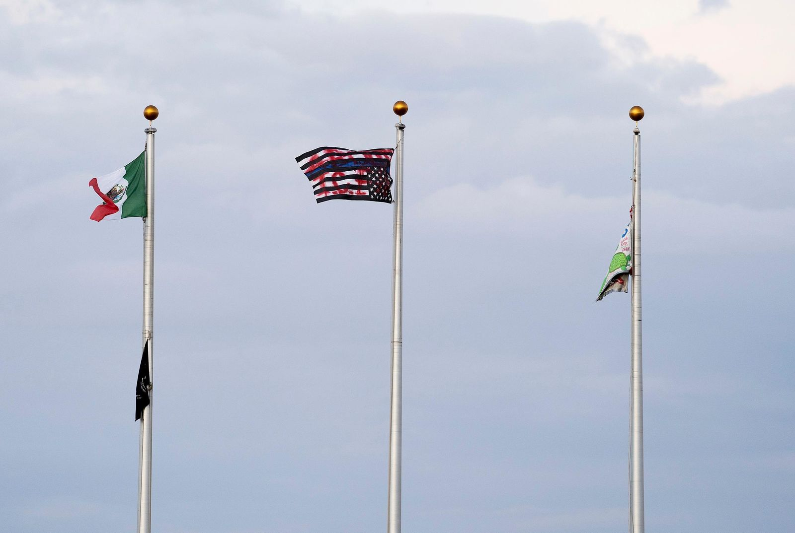 This Friday, July 12, 2019, photo shows a Mexican flag, from left, an upside down U.S. flag with a blue line and graffiti on it and a protesting banner after the Colorado state flag, the American flag and the GEO company flag were dropped and replaced, while hundreds of protesters assembled for a march at the GEO facility in Aurora, Colo. Police say they will be reviewing any available video to help them identity protesters who trespassed and pulled down the American flag in front of an immigration detention center in suburban Denver, tried to burn it and replaced it with a Mexican flag. (Philip B. Poston/The Aurora Sentinel via AP)