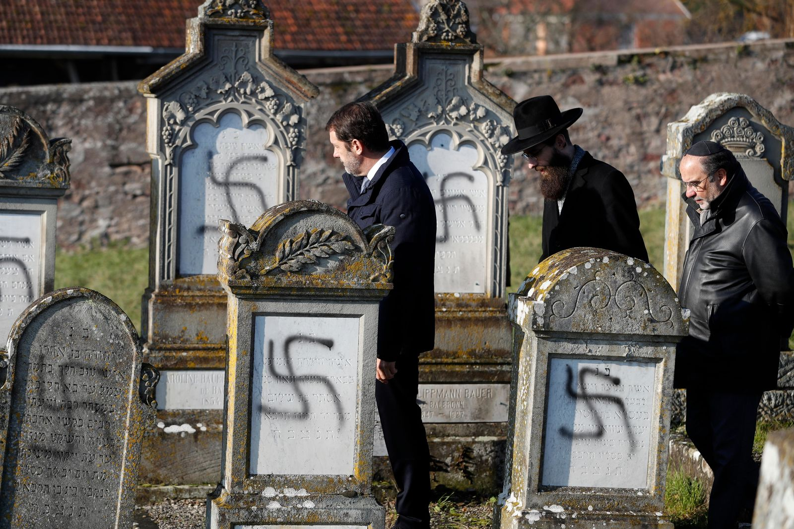 French Interior Minister Christophe Castaner, center, followed by Strasbourg chief Rabbi Harold Abraham Weill, second right, walk amid vandalized tombs in the Jewish cemetery of Westhoffen, west of the city of Strasbourg, eastern France, Wednesday, Dec. 4, 2019.{ } (AP Photo/Jean-Francois Badias)