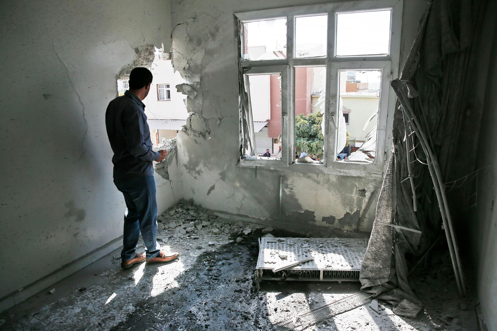 A person inspects the damage on a building hit by a mortar fired from inside Syria, in Akcakale, Sanliurfa province, southeastern Turkey, Sunday, Oct. 13, 2019. (AP Photo/Lefteris Pitarakis)