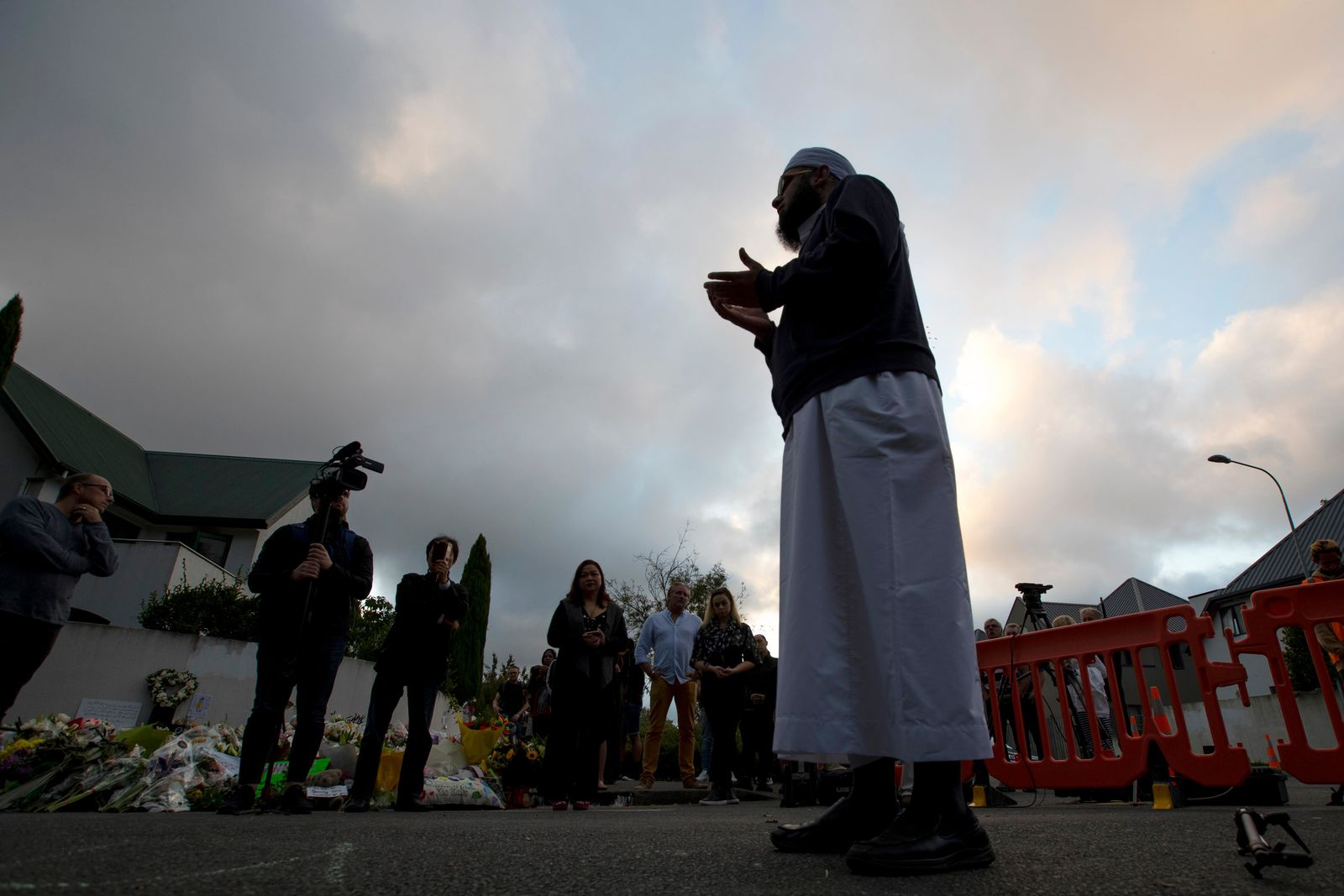 A Muslim offers prayer near the main road to the Al Noor mosque in Christchurch, New Zealand, Tuesday, March 19, 2019. (AP Photo/Vincent Thian)