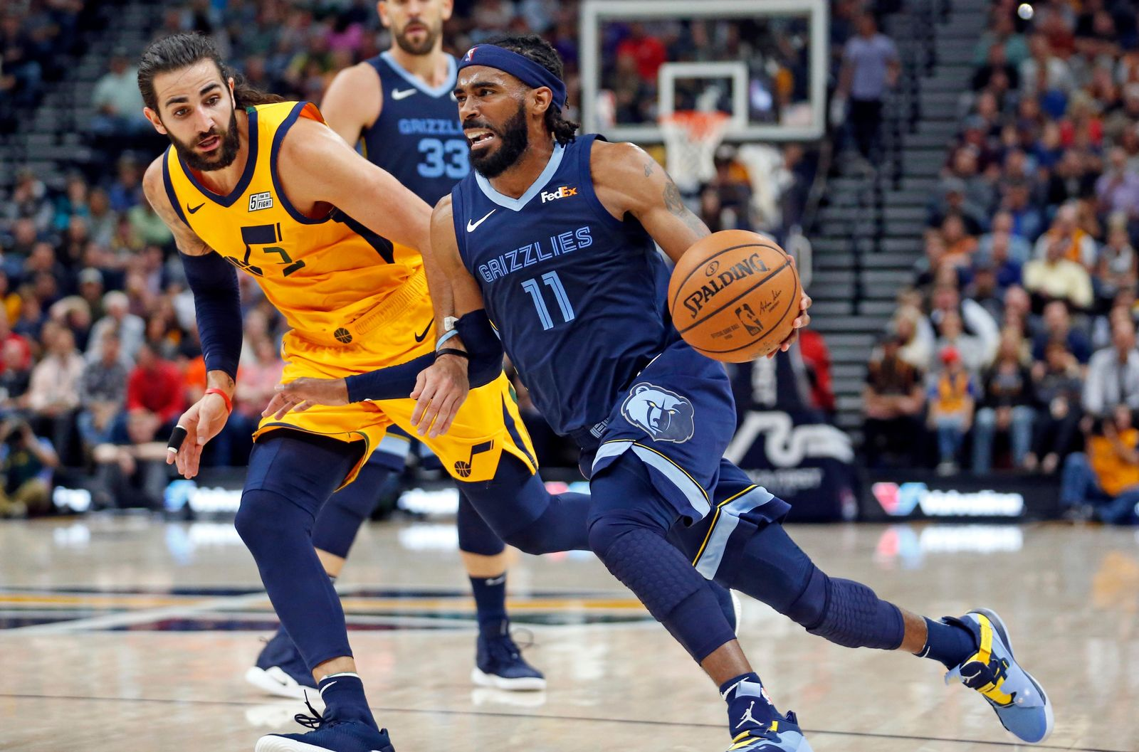 Memphis Grizzlies guard Mike Conley (11) drives to the basket as Utah Jazz guard Ricky Rubio, rear, defends in the first half of an NBA basketball game, Monday, Oct. 22, 2018, in Salt Lake City. (AP Photo/Rick Bowmer)