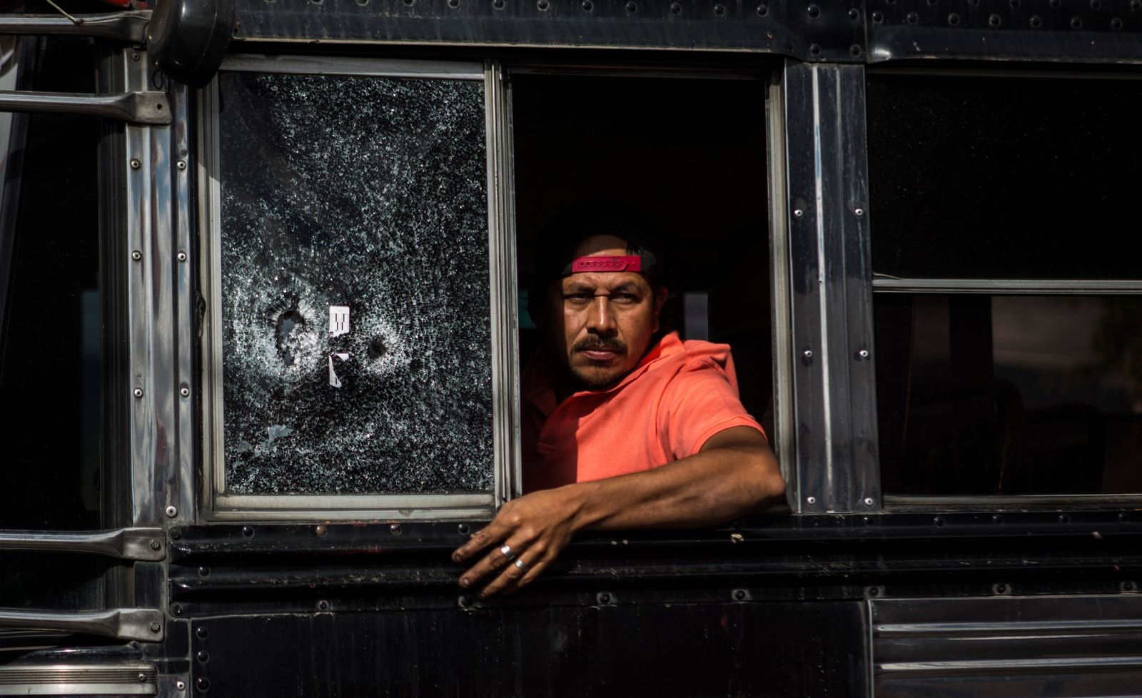 A bus driver peers from his window, which he said was shot a few weeks ago, as he drives slowly through a security checkpoint in the El Milagro area of the Mixco municipality on the outskirts of Guatemala City, Friday, Jan. 17, 2020. Guatemala's new president announced a state of alert for two municipalities with high crime rates to combat gang activity Friday, a measure that allows the deployment of military troops. (AP Photo/Oliver de Ros)
