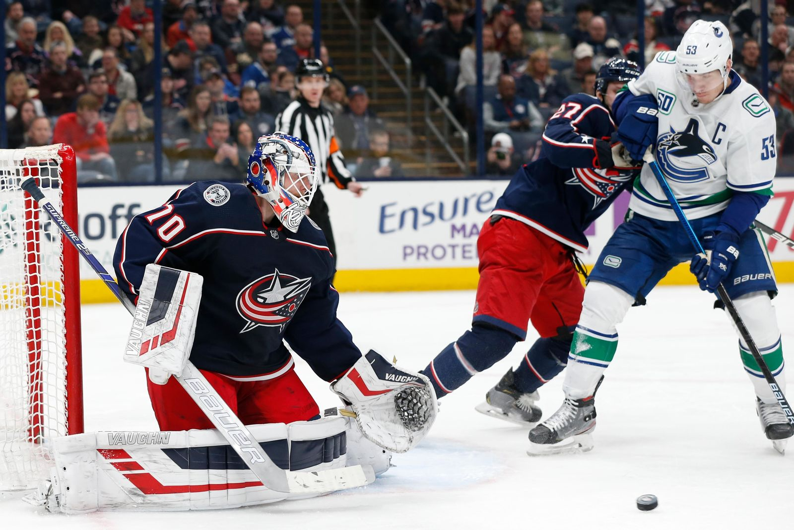 Columbus Blue Jackets' Joonas Korpisalo, left, of Finland, makes a save as teammate Ryan Murray, center, and Vancouver Canucks' Bo Horvat fight for position during the third period of an NHL hockey game Sunday, March 1, 2020, in Columbus, Ohio. The Blue Jackets defeated the Canucks 5-3. (AP Photo/Jay LaPrete)