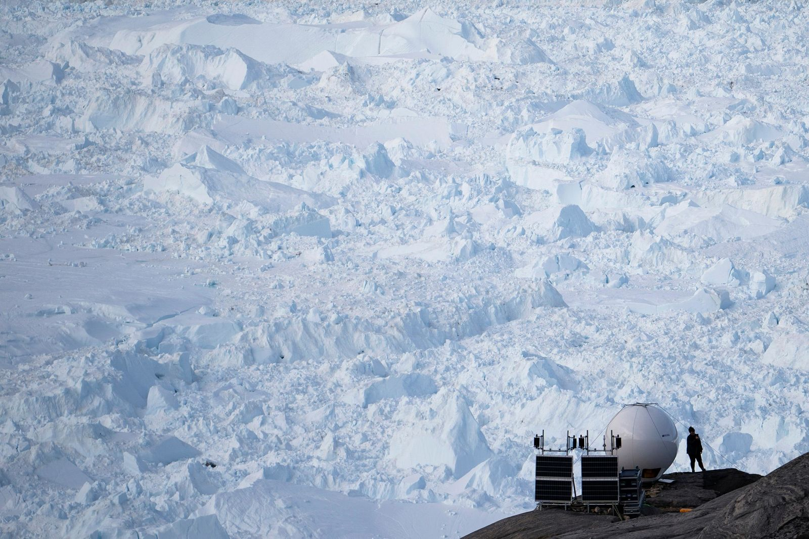 In this Aug. 16, 2019, photo, a woman stands next to an antenna at an NYU base camp at the Helheim glacier in Greenland. Summer 2019 is hitting the island hard with record-shattering heat and extreme melt.{ } (AP Photo/Felipe Dana)