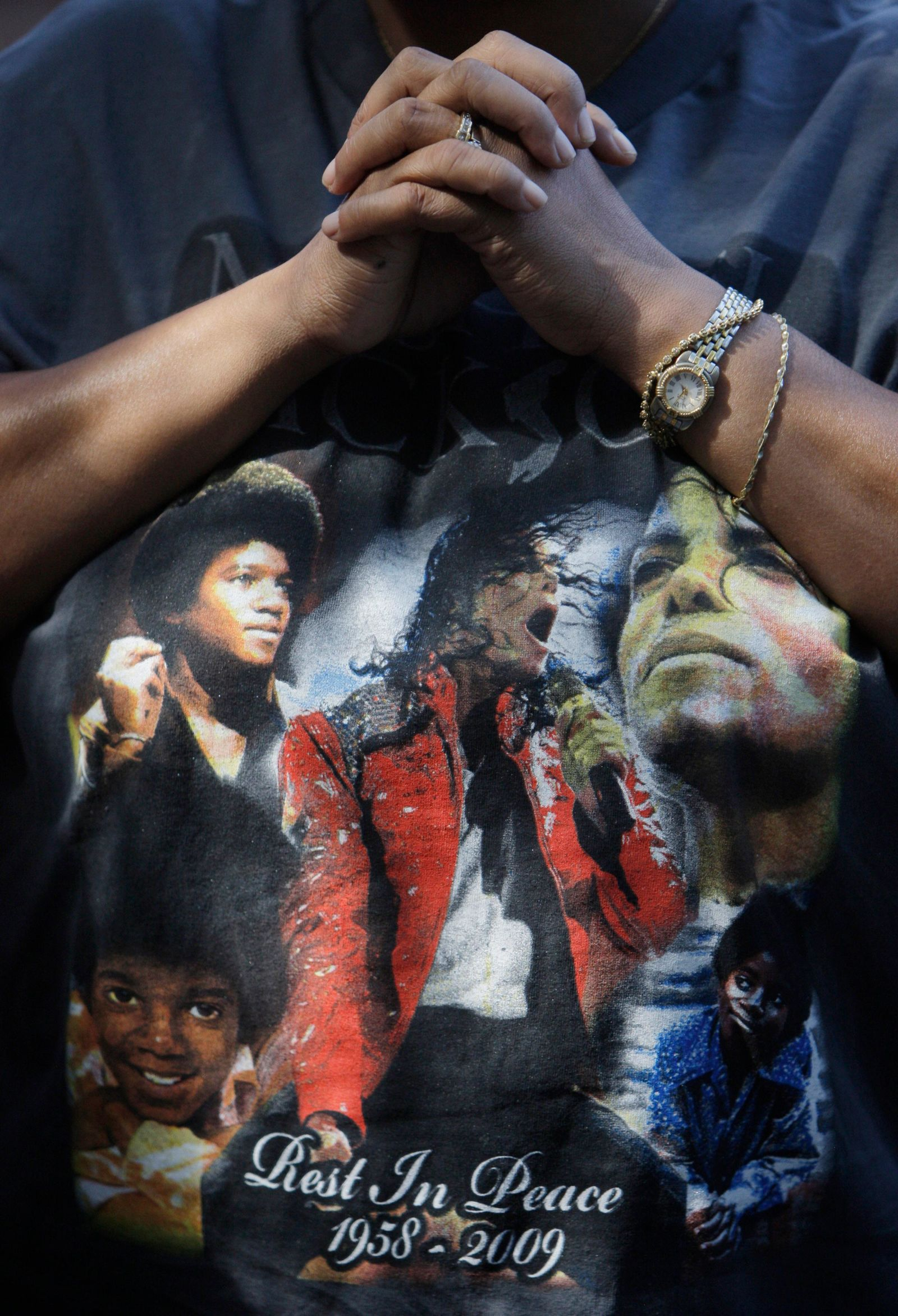 FILE - This June 30, 2009 file photo shows a fan wearing a Michael Jackson T-shirt at a makeshift memorial for the late pop star outside the Jackson family home in Encino section of Los Angeles. Tuesday, June 25, 2019, marks the tenth anniversary of Jackson's death. (AP Photo/Jae C. Hong, File)