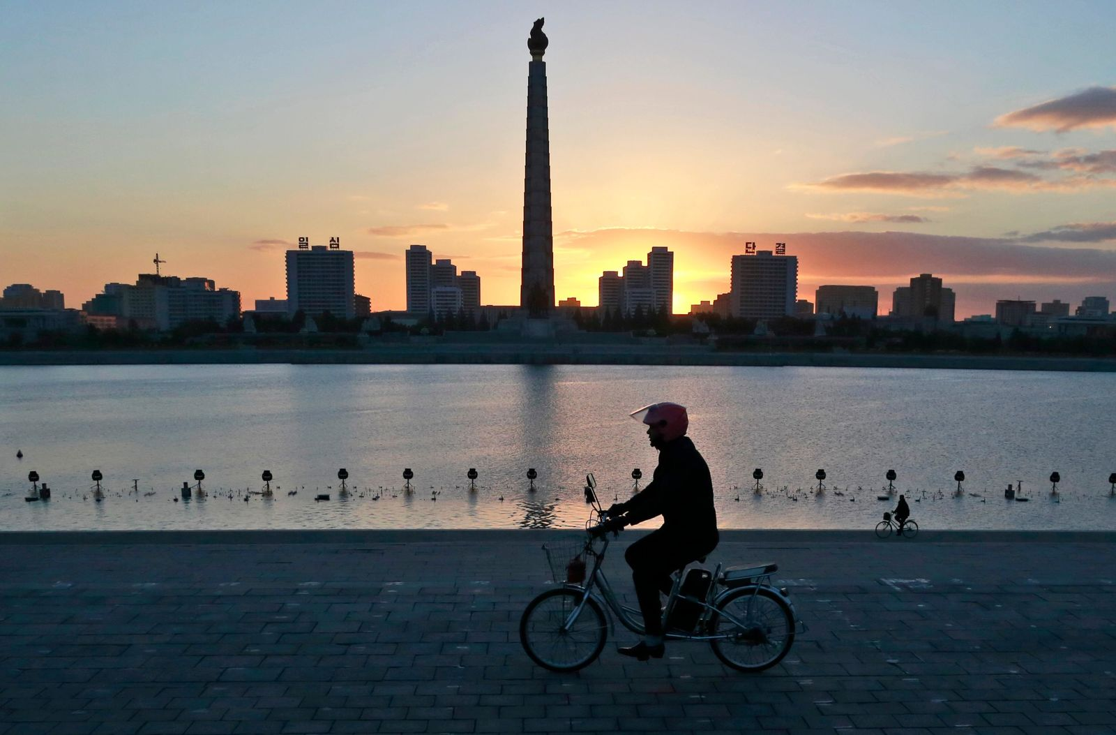 FILE - In this Oct. 27, 2018 file photo, a man rides his electric bike as the Tower of the Juche Idea is silhouetted agains the sunrise in Pyongyang, North Korea. As Chinese President Xi Jinping makes an official trip June 20, 2019 to{ } (AP Photo/Dita Alangkara, File)