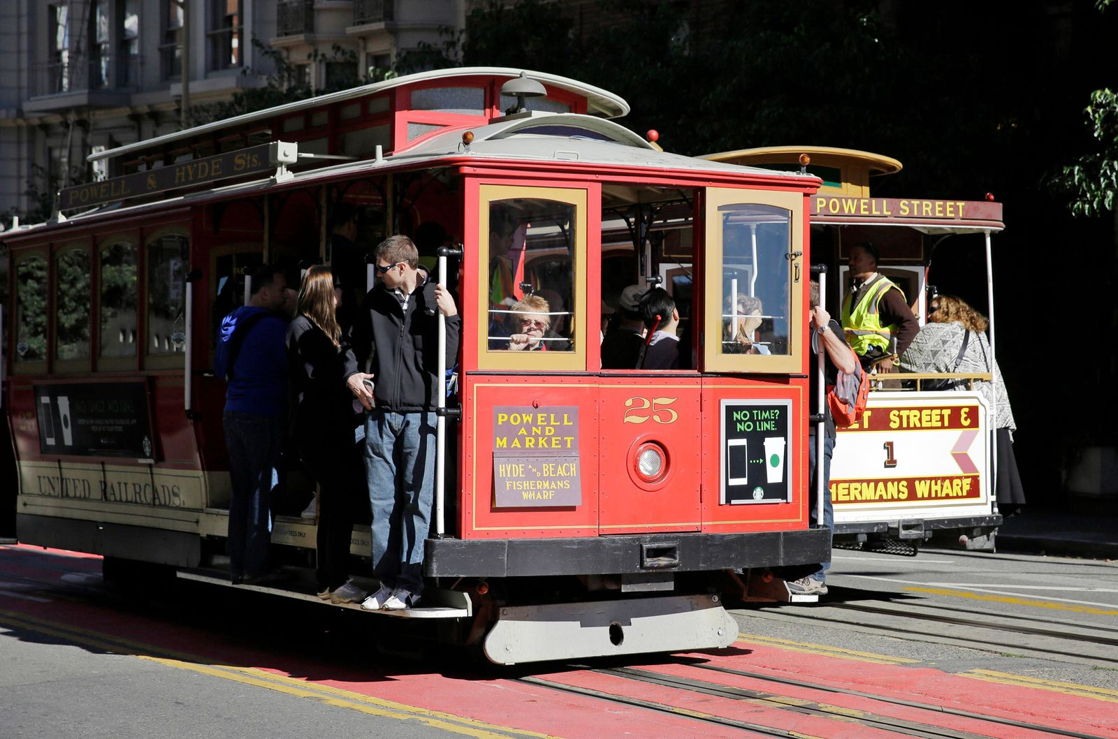 FILE - In this Nov. 3, 2015 file photo, a pair of cable cars go past each other on Powell Street atop Nob Hill in San Francisco. (AP Photo/Eric Risberg, File)