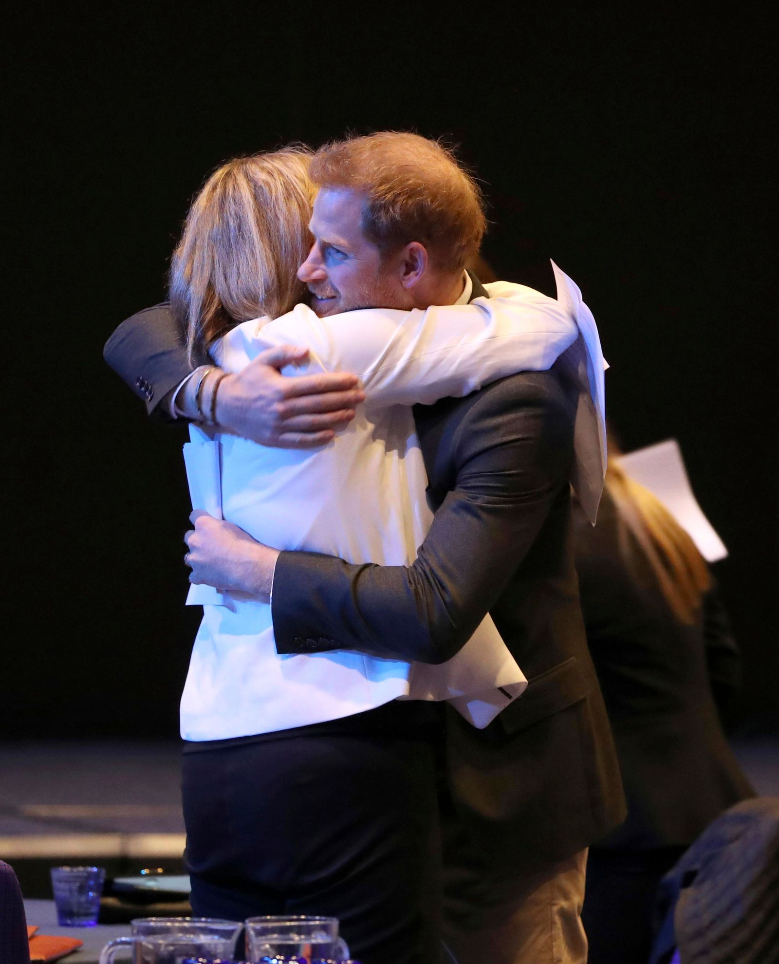 Britain's Prince Harry is hugged, during a sustainable tourism summit at the Edinburgh International Conference Centre in Edinburgh, Scotland, Wednesday, Feb. 26, 2020. (Andrew Milligan/Pool Photo via AP)